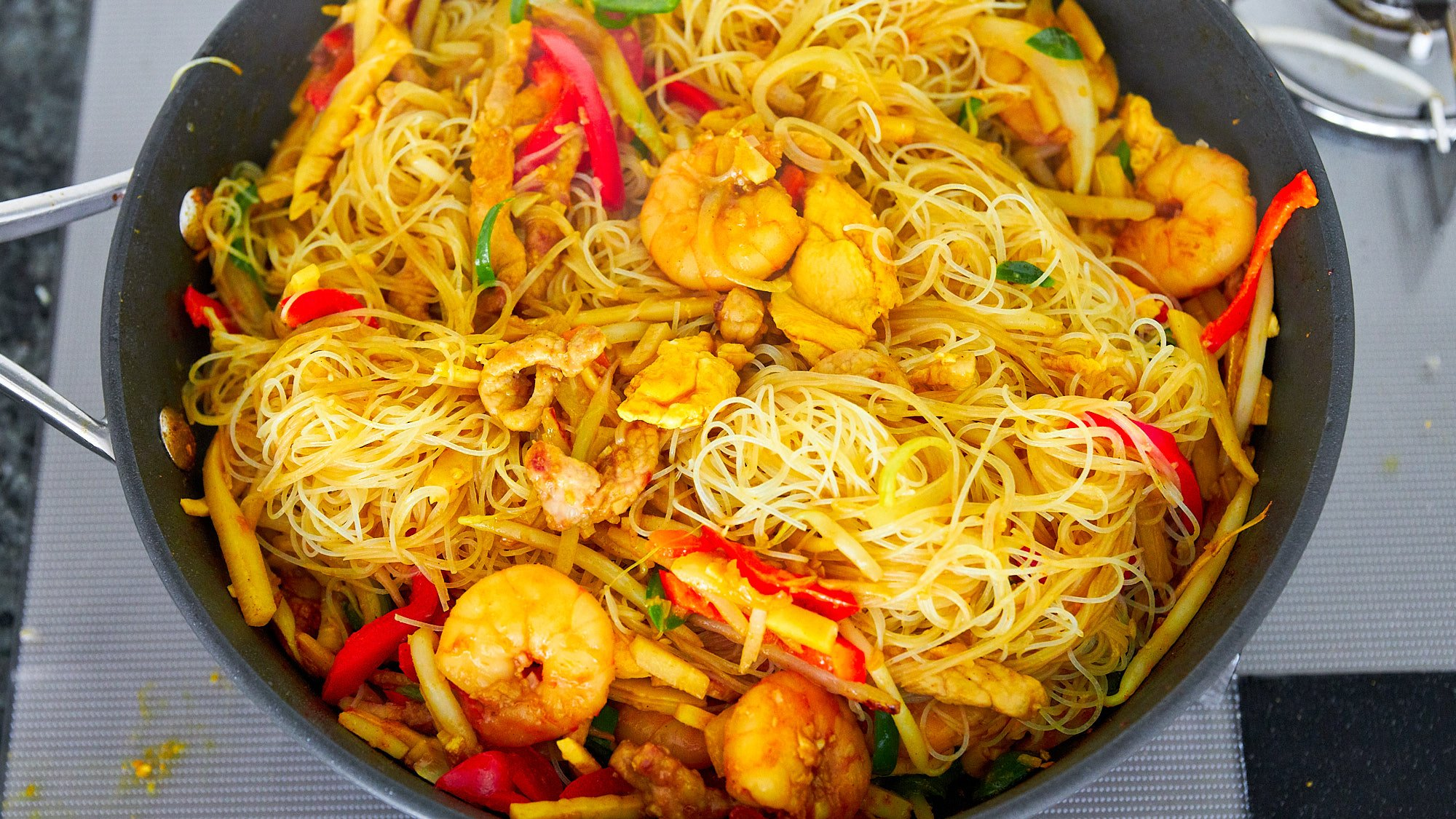 Toss the rice vermicelli with the vegetables, seafood and curry sauce.