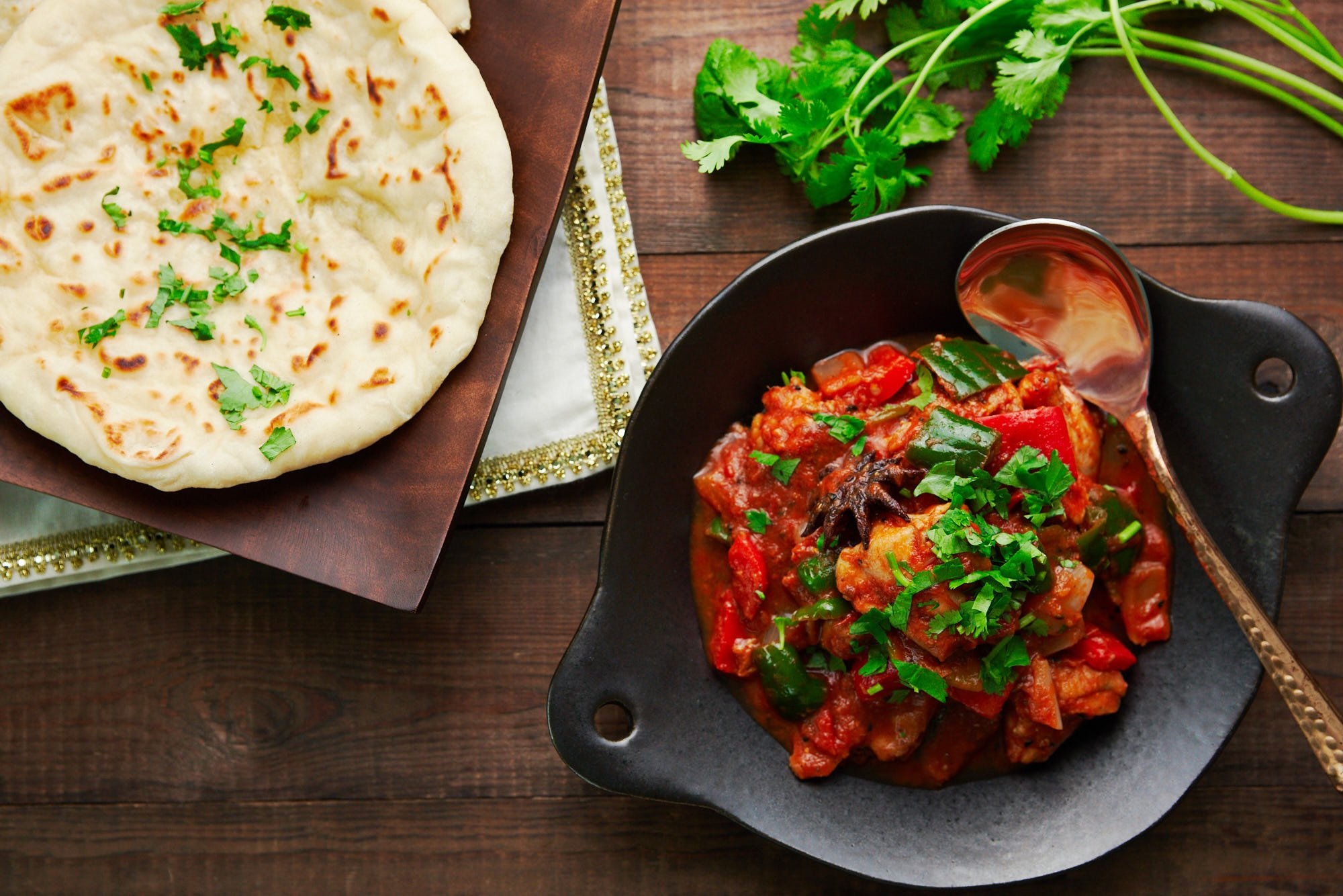 Buttered naan on a wooden plate with a serving of Chicken Jalfrezi with peppers, onions, and tomatoes.