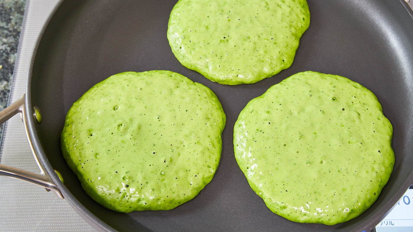 Green matcha panckaes in a pan.