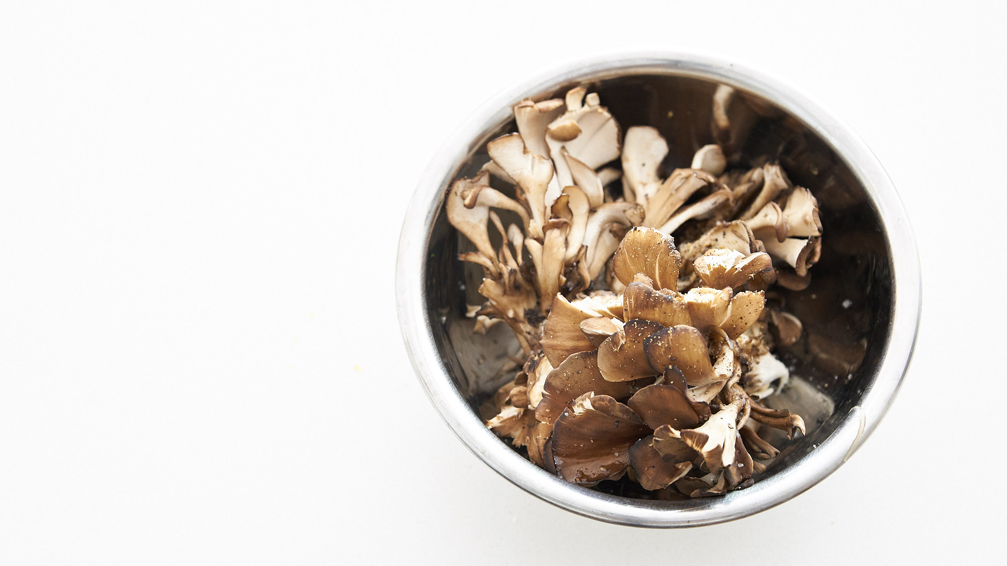 Maitake mushrooms tossed with olive oil, salt and pepper, ready to be roasted.