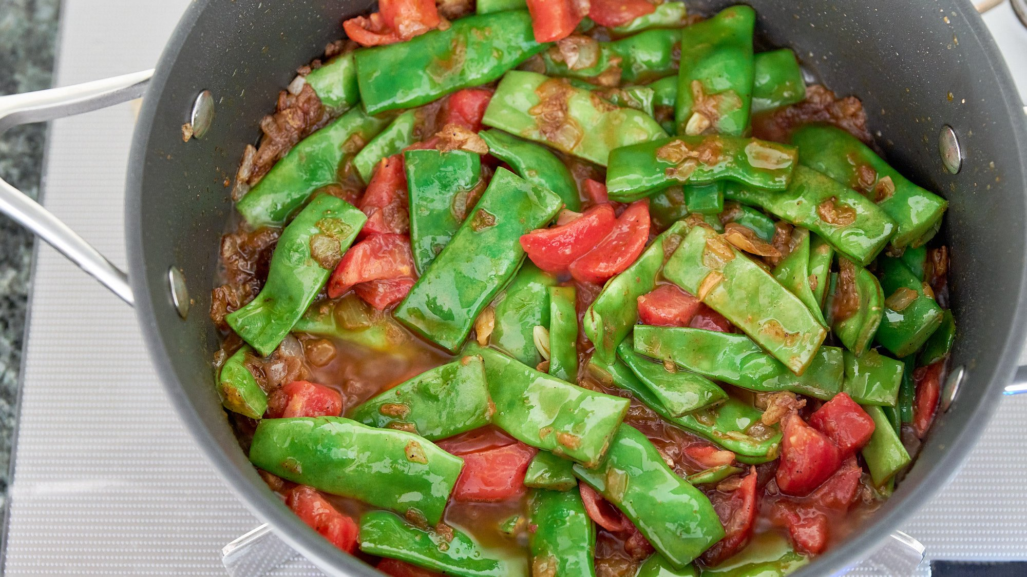 Add the tomatoes to the Loubieh Bi Zeit.