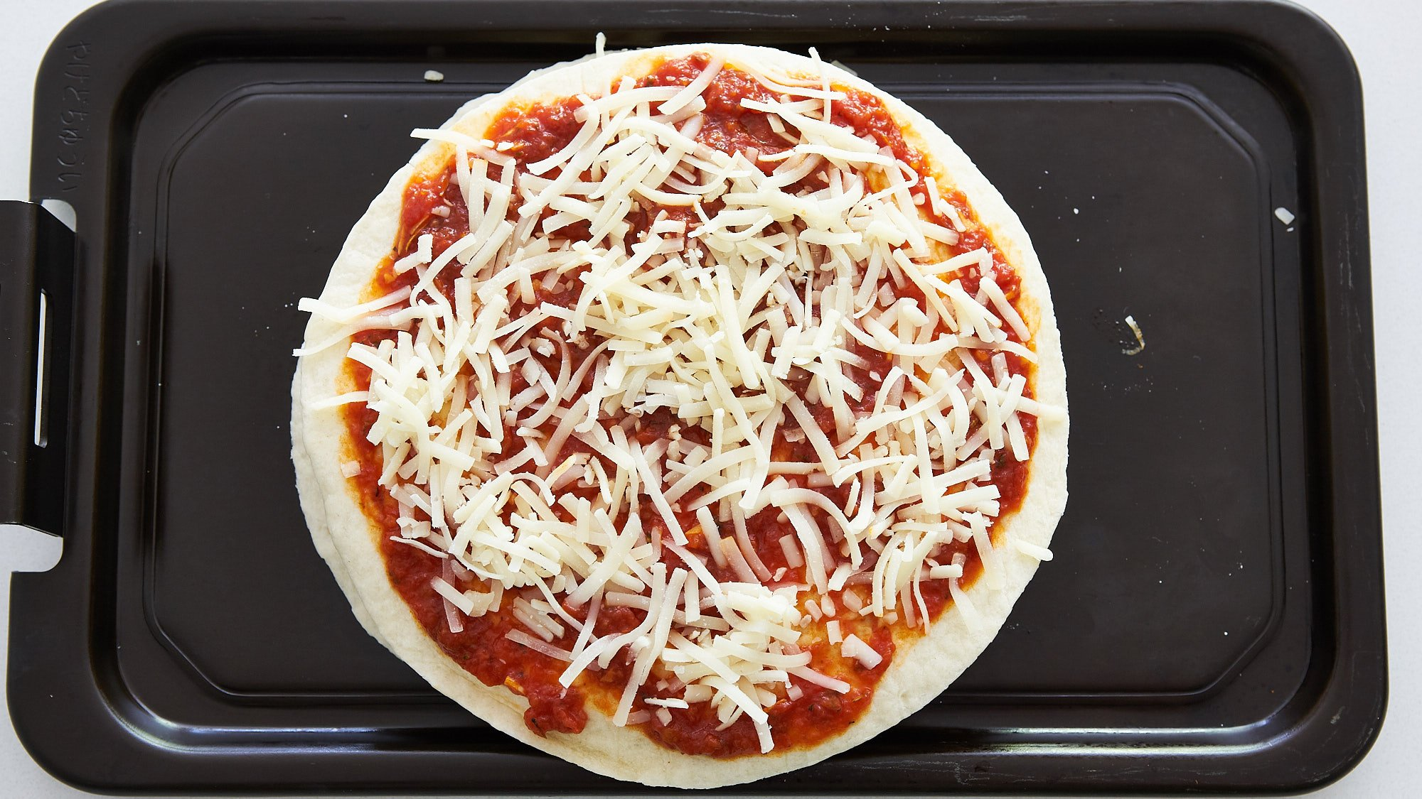Another tortilla and pizza sauce go on top, along with another layer of cheese.