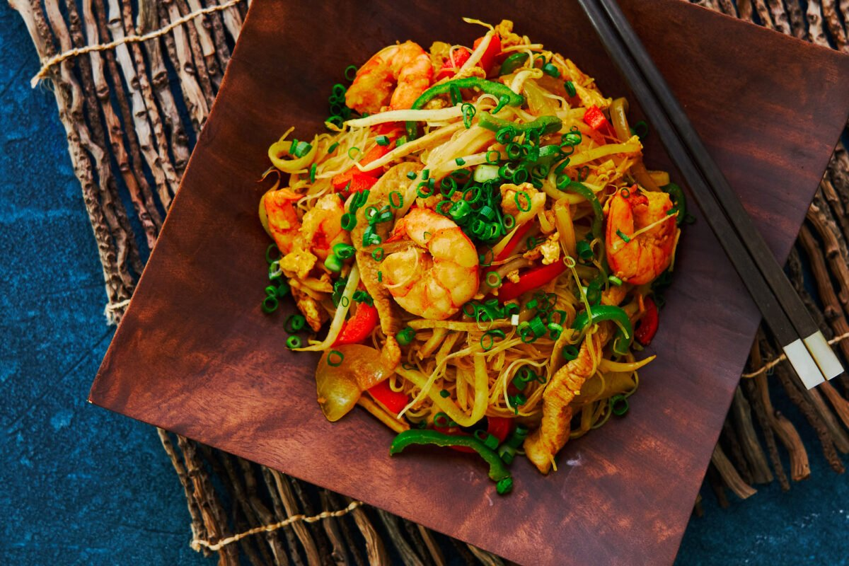 "A Chinese-American classic, these ""Singapore"" Noodles are loaded with shrimp pork and vegetables, stir-fried with curry-flavored rice noodles."