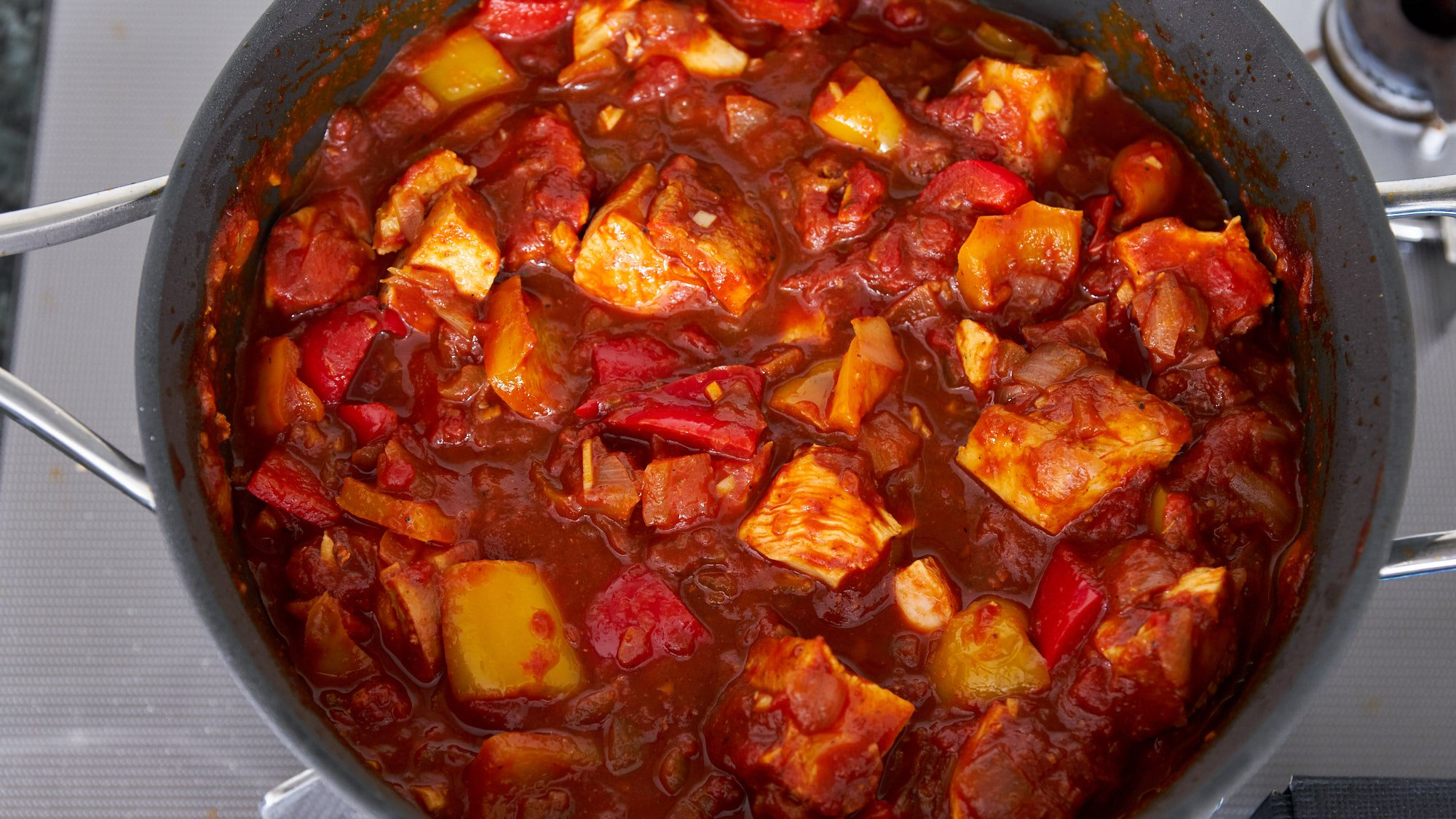 The chicken is returned to the pot with the chili and simmered until the chicken is cooked through.