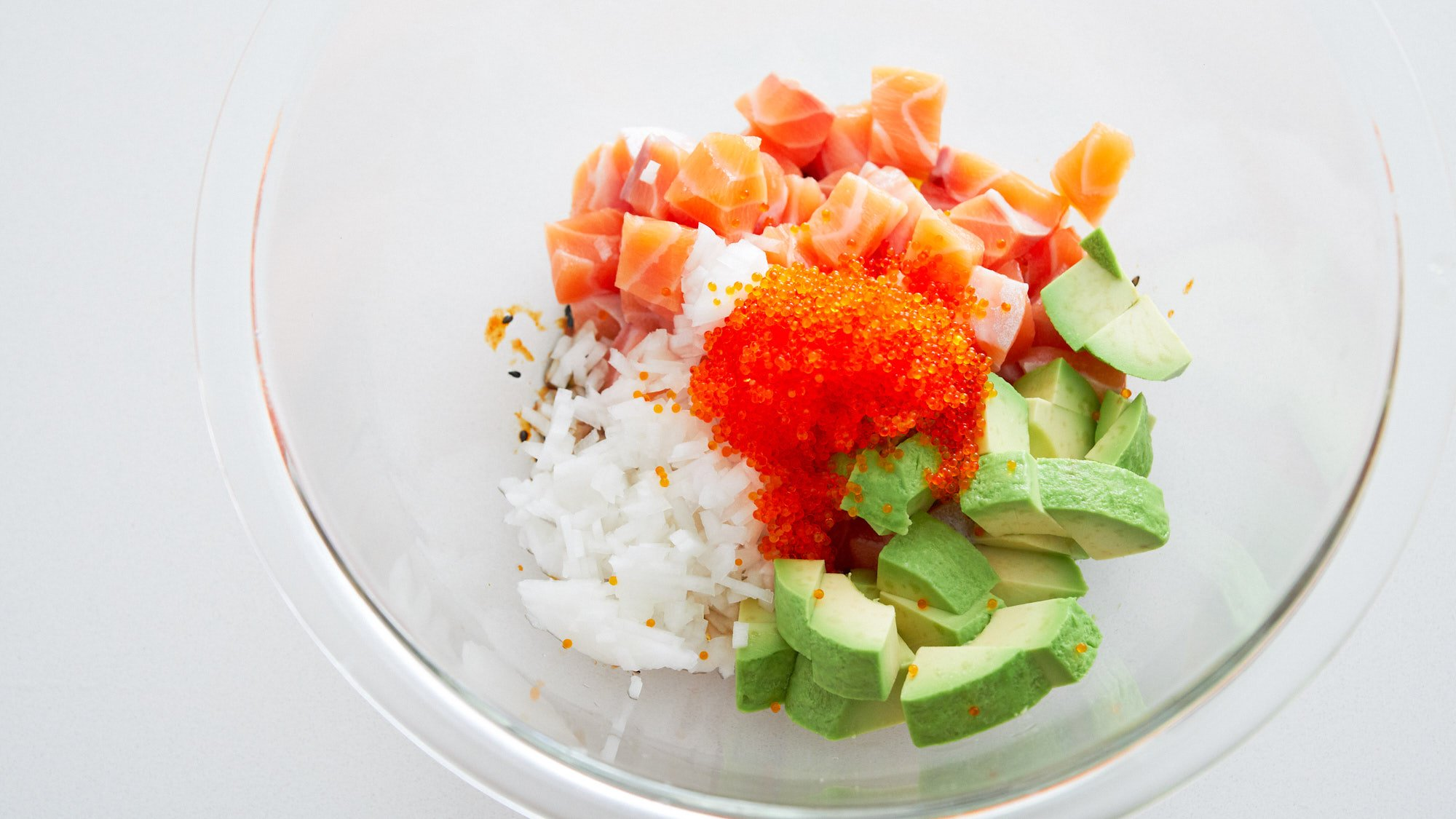 Ingredients for spicy salmon poke. Raw salmon, sweet onions, avocado, and tobiko.