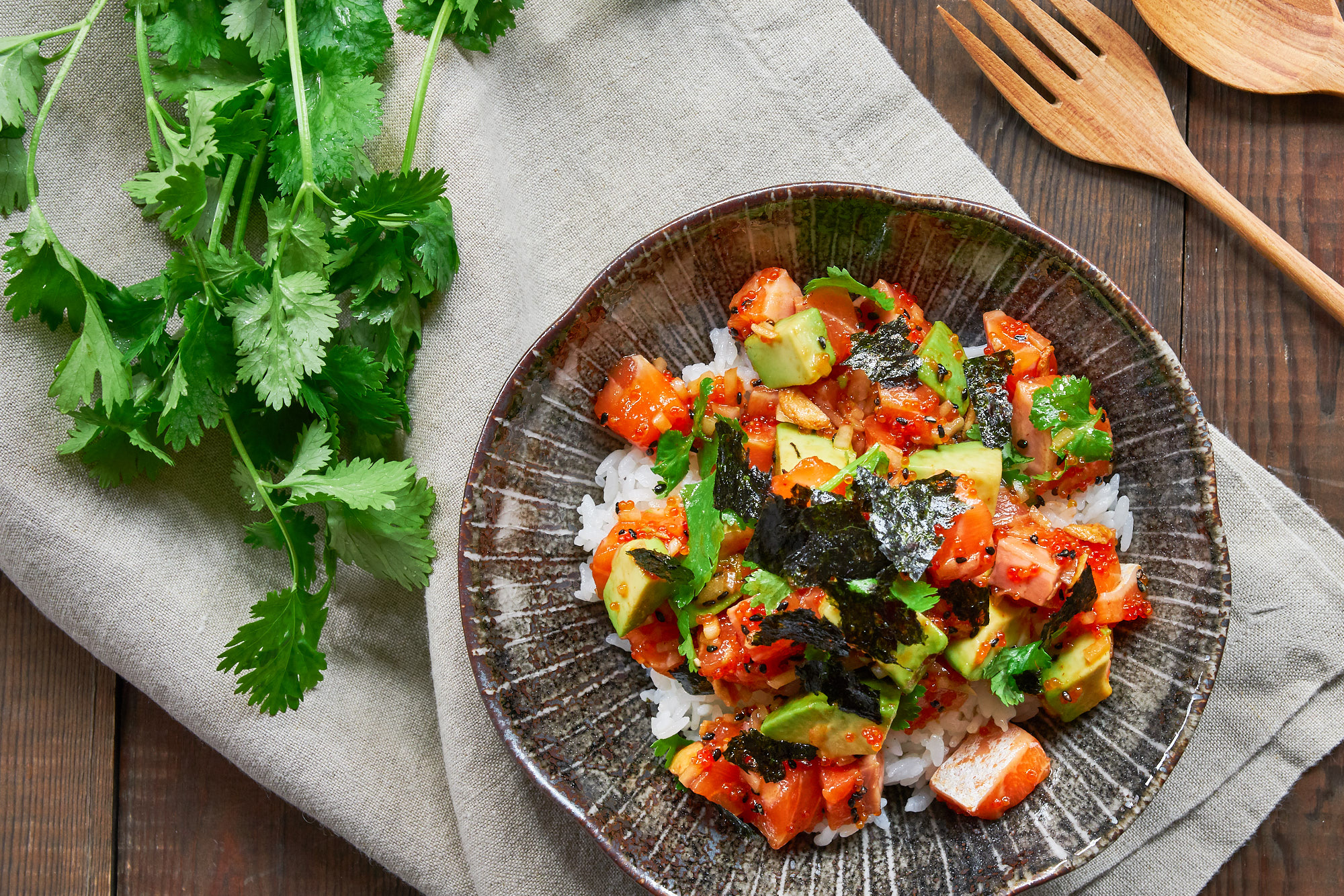 The best Spicy Salmon Poke recipe. Rich salmon and creamy avocado marinated with a sesame sriracha sauce and mixed with crunchy tobiko, crisp sweet onions and fresh cilantro served over a bowl of hot rice.