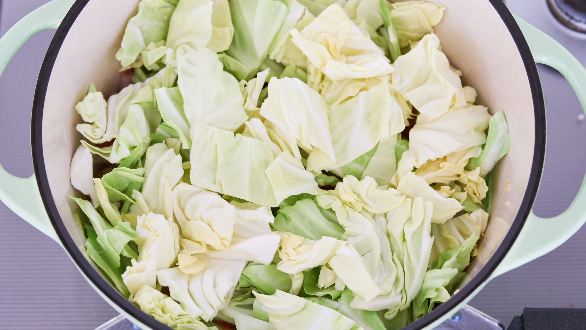 Pieces of cabbage in a green dutch oven.