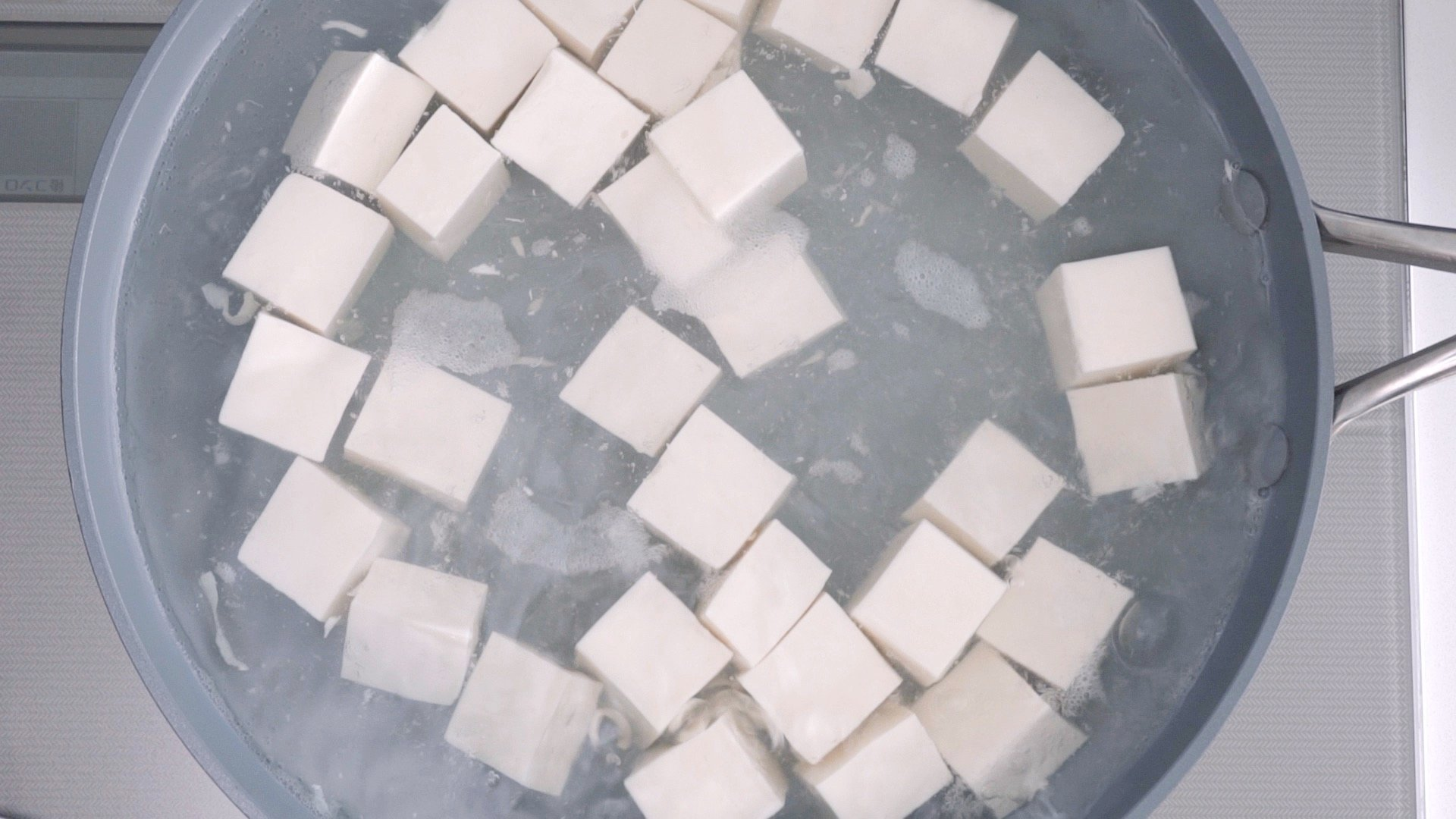 Blanche the tofu in salted water to remove any excess water.