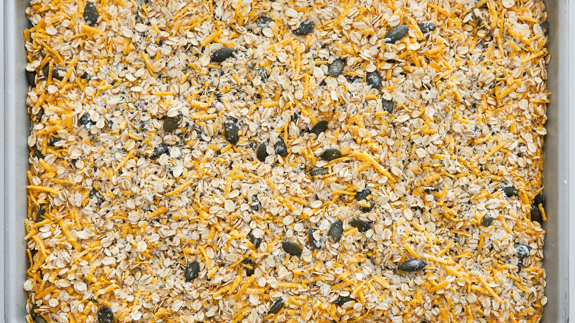 Cheese and savory granola mixture spread out on a baking sheet.