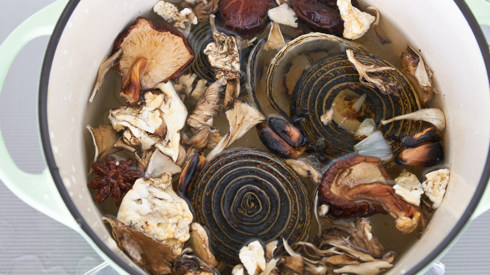 Dried shiitake and maitake mushrooms with charred aromatics and spices for making vegan pho broth.