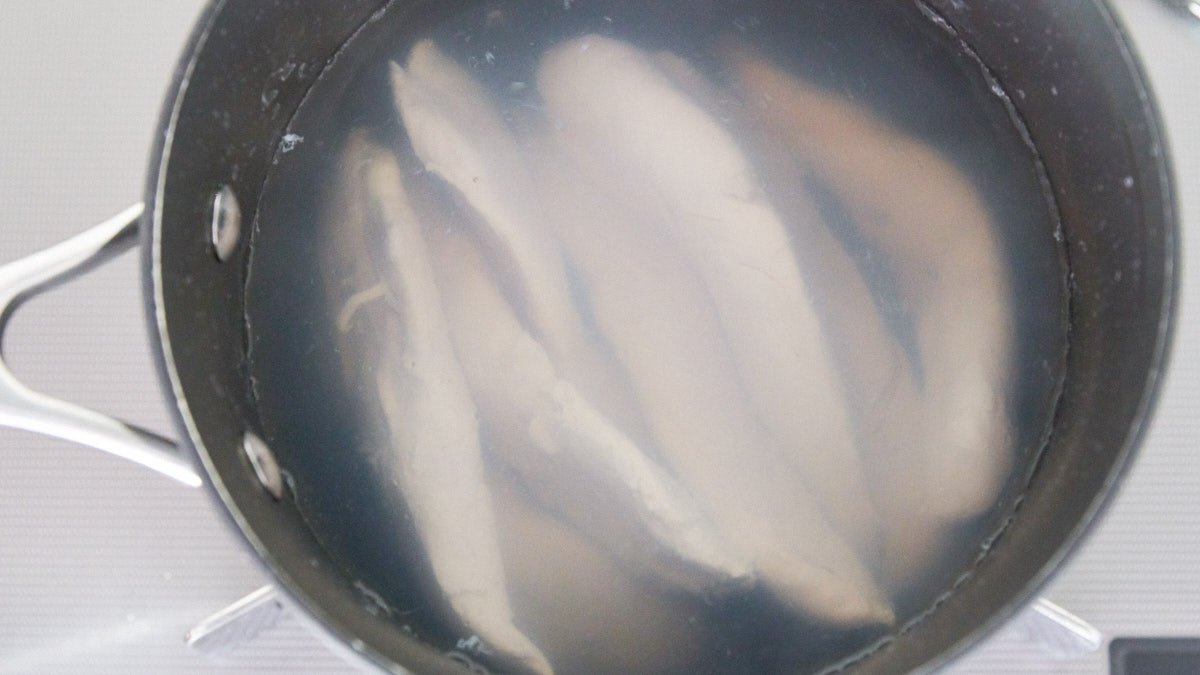 Chicken tenders poaching in a pot of hot water.