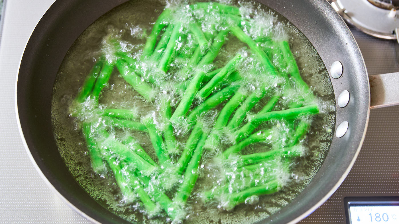Oil blanching green beans before stir-frying them tenderizes them, while retaining their color.
