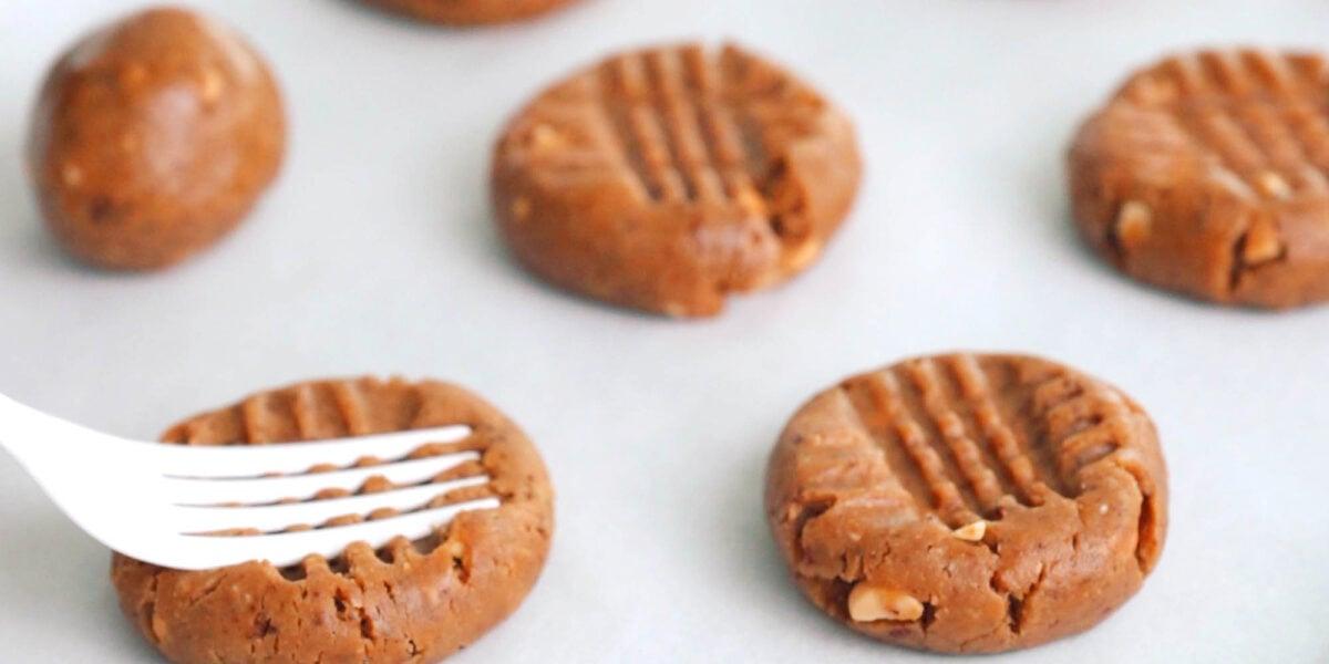 Flattening Peanut Butter Cookie dough with a fork.