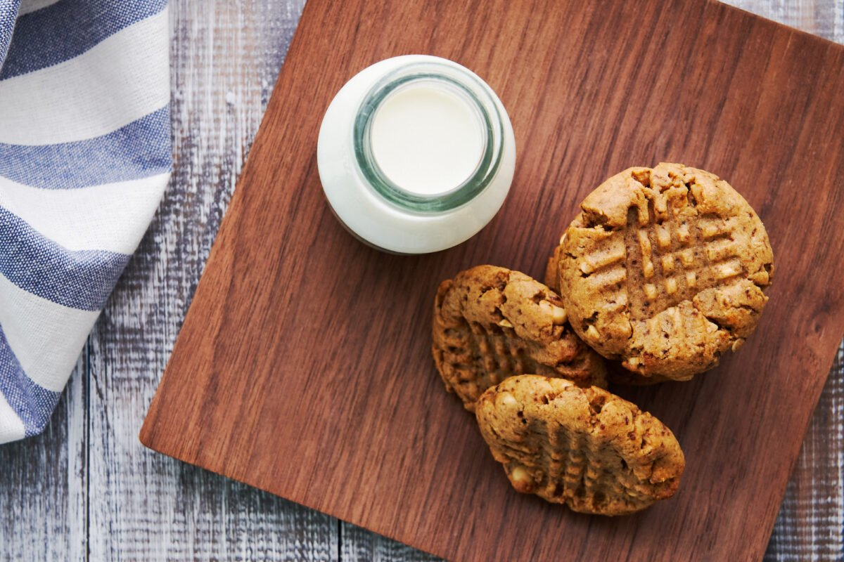 Healthy plant-based Peanut Butter Cookies on a wooden plate with almond milk.