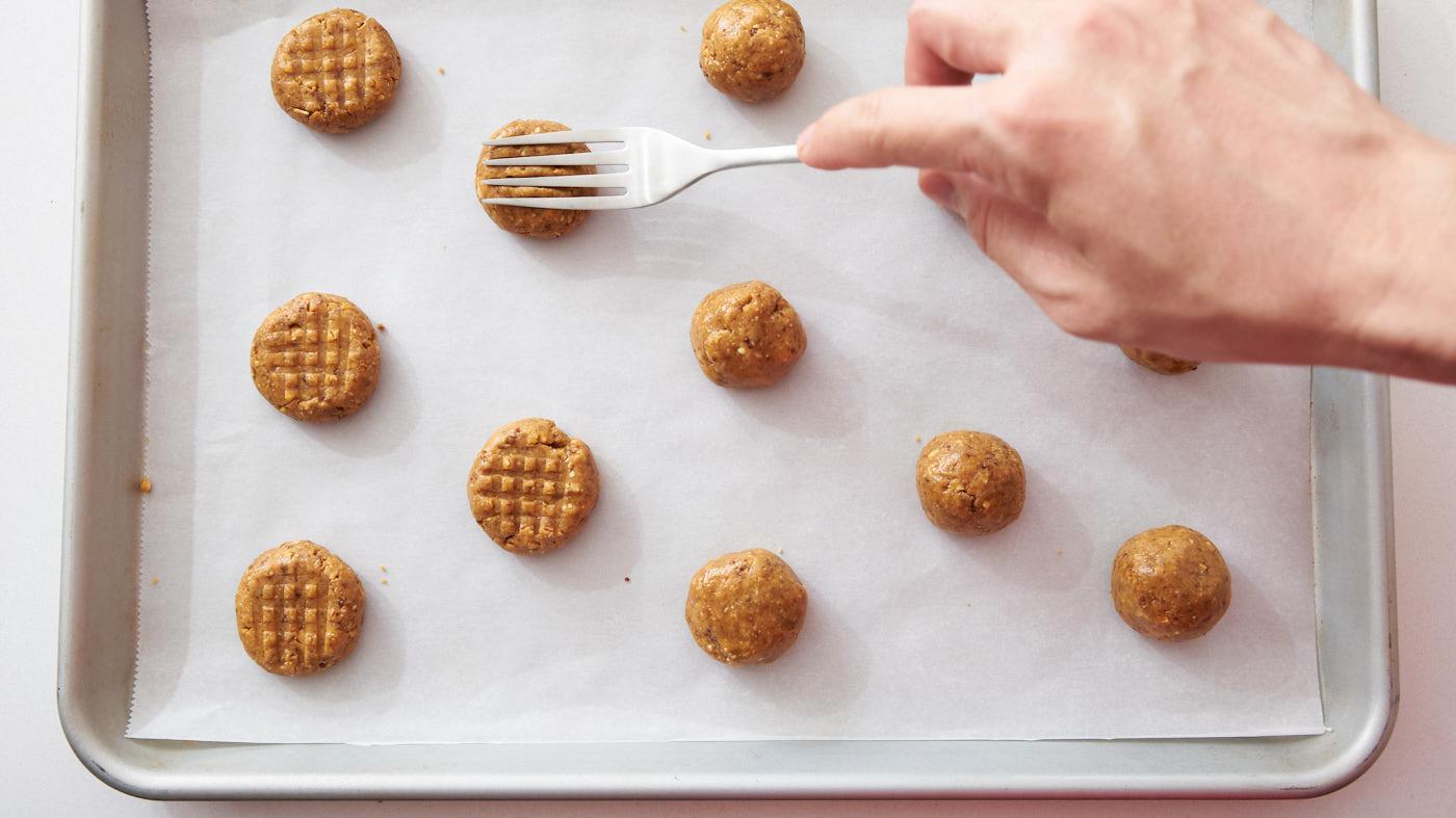 Vegan peanut butter cookie dough flattened with a cross hatch pattern using a fork.