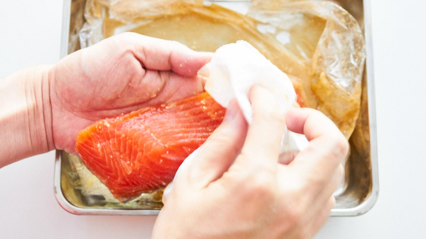 Removing the excess miso marinade from salmon fillets using paper towels.