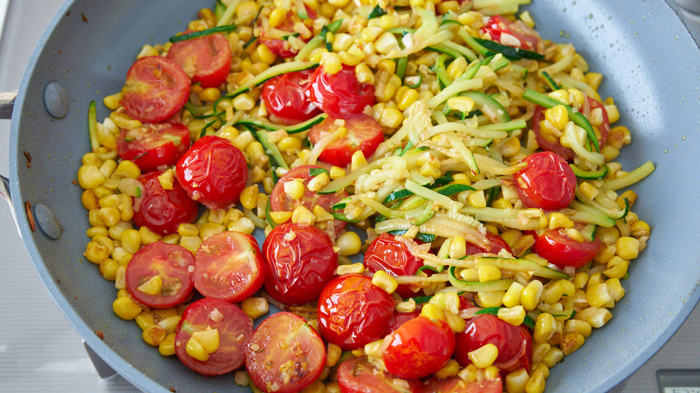 Pan-roasted cherry tomatoes with corn and zucchini for Summer Pasta.