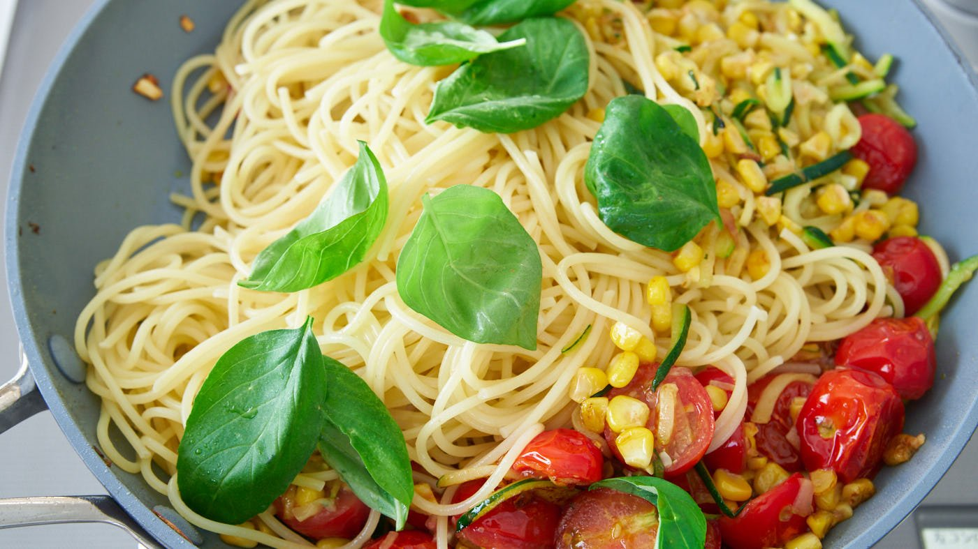 Basil and spaghettini being tossed with pan-roasted tomatoes, corn, and zucchini for Pasta Estate (Summer Pasta).