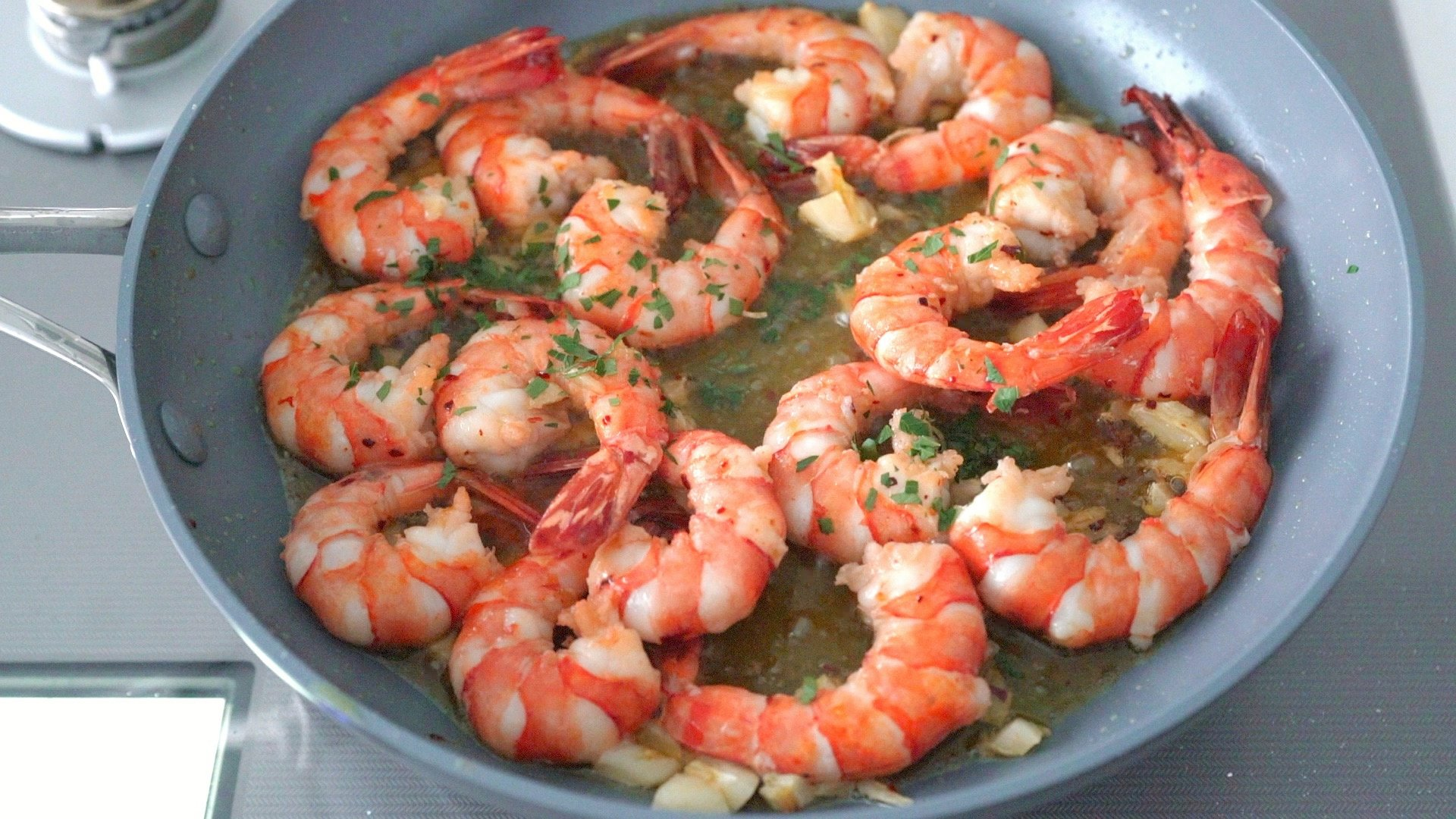 Spanish Garlic Shrimp (Gambas al Ajillo) in a frying pan garnished with parsley.