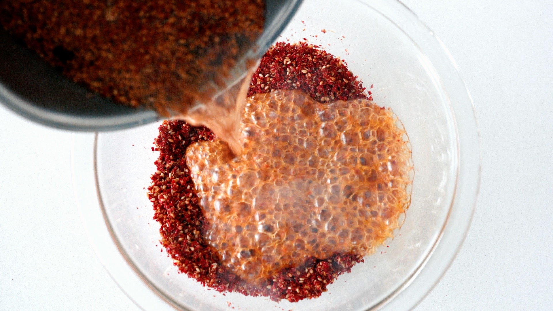 Infusing hot oil with chili pepper flakes for making Sichuan Chili Oil.