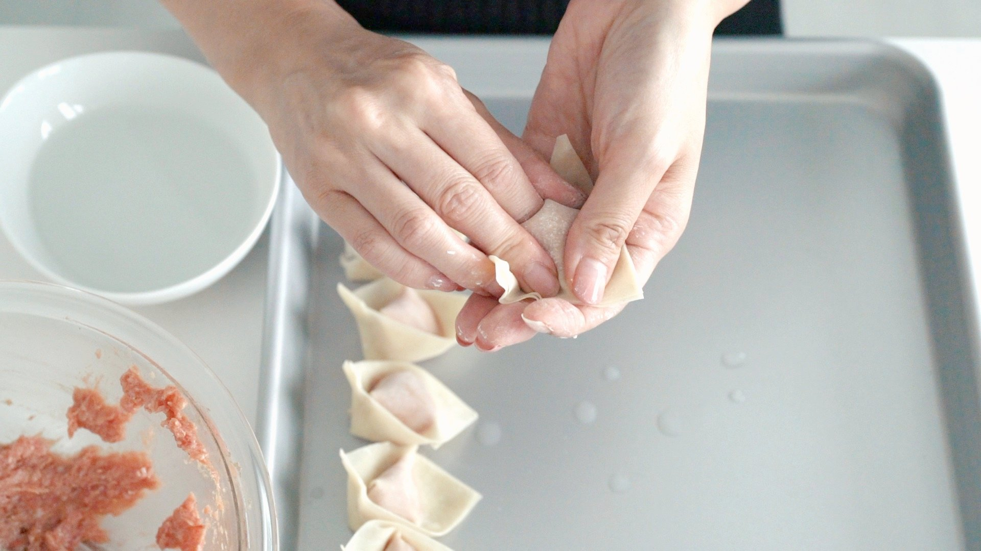 Sealing the wonton shut.