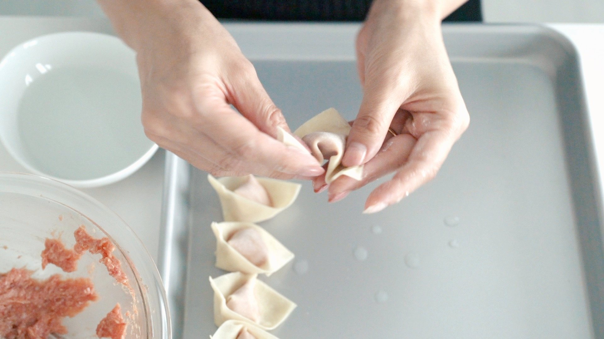 "Giving the wontons their ""crossed hands"" shape"