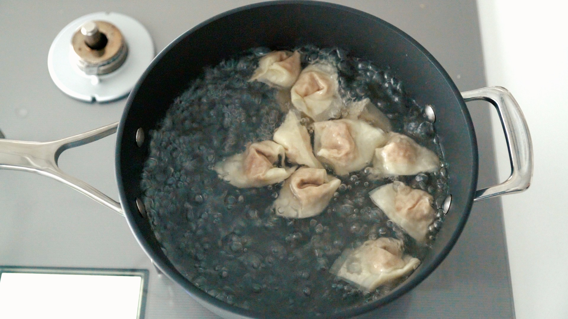 Boiling Chengdu-style wontons in chili oil.