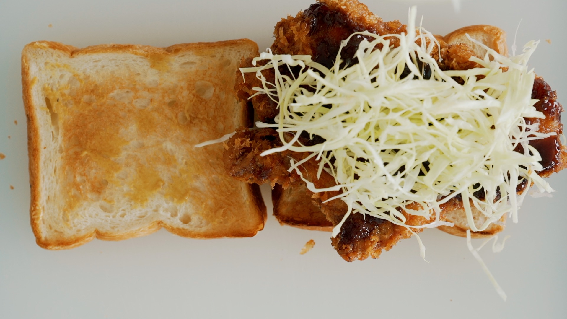 Topping the Katsu Sando with cabbage.