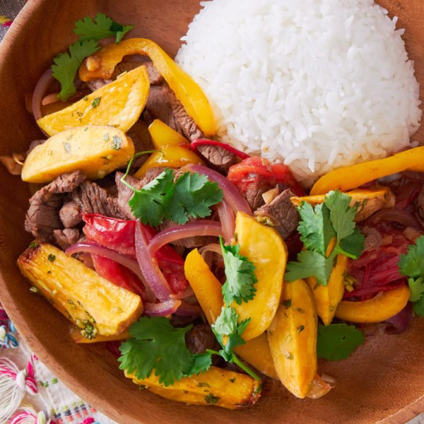 With tender beef marinated in soy sauce and pisco, Lomo Saltado is a delicious Peruvian-Chinese stir-fry that's loaded with potatoes, onions, tomatoes, and garlic.