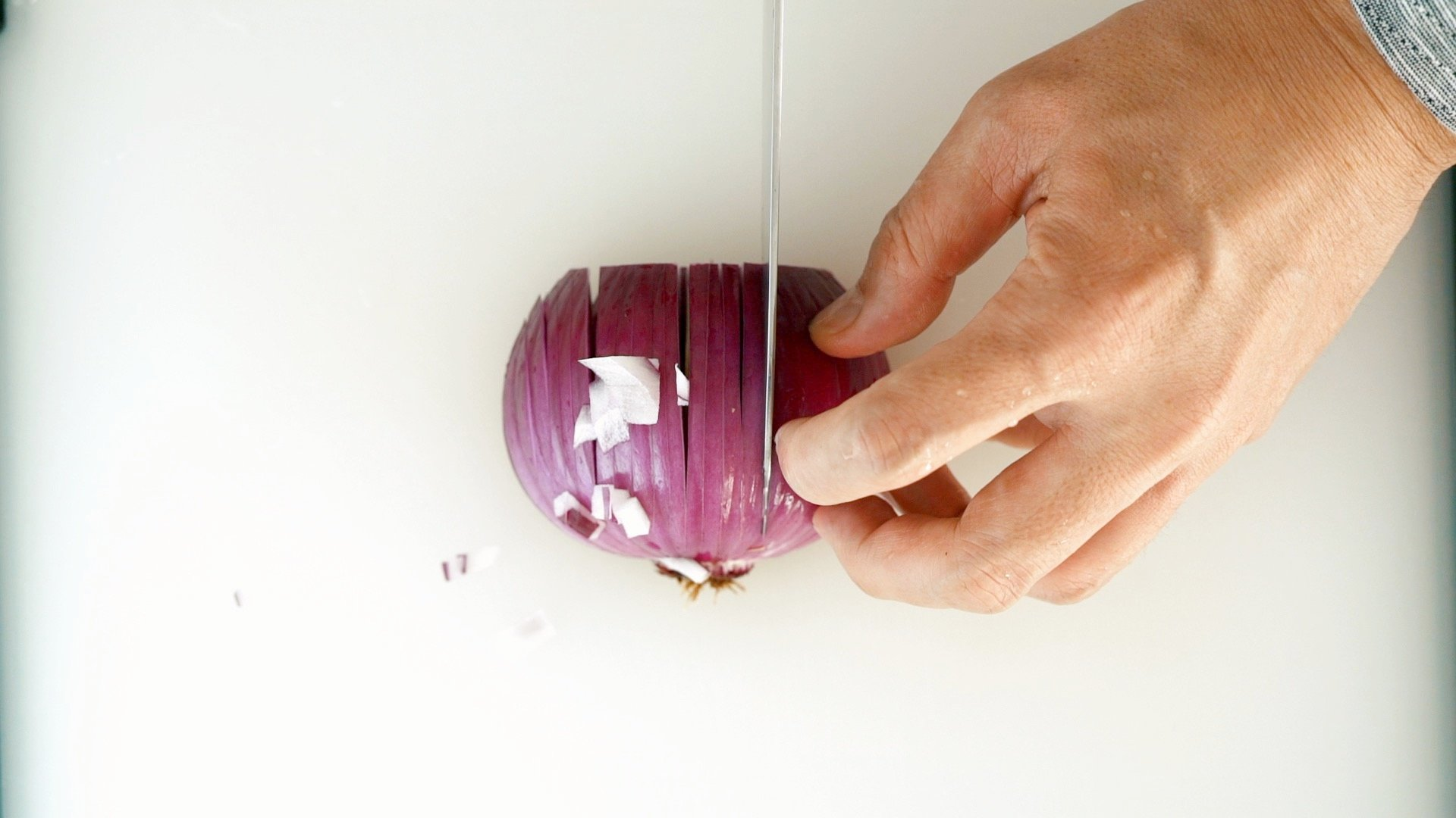 Cutting vertical slits in an onion.