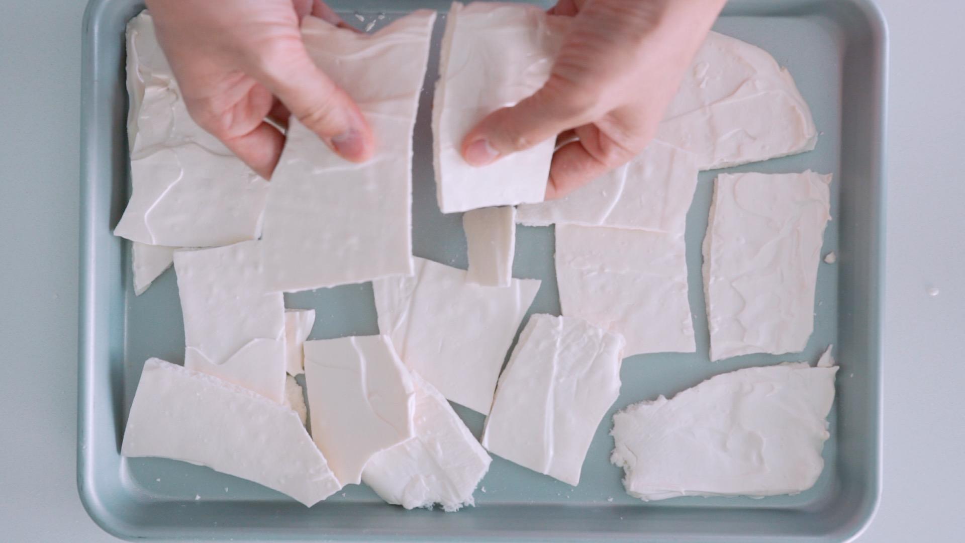 Breaking crisp meringue into small sheets for making Eton Mess.