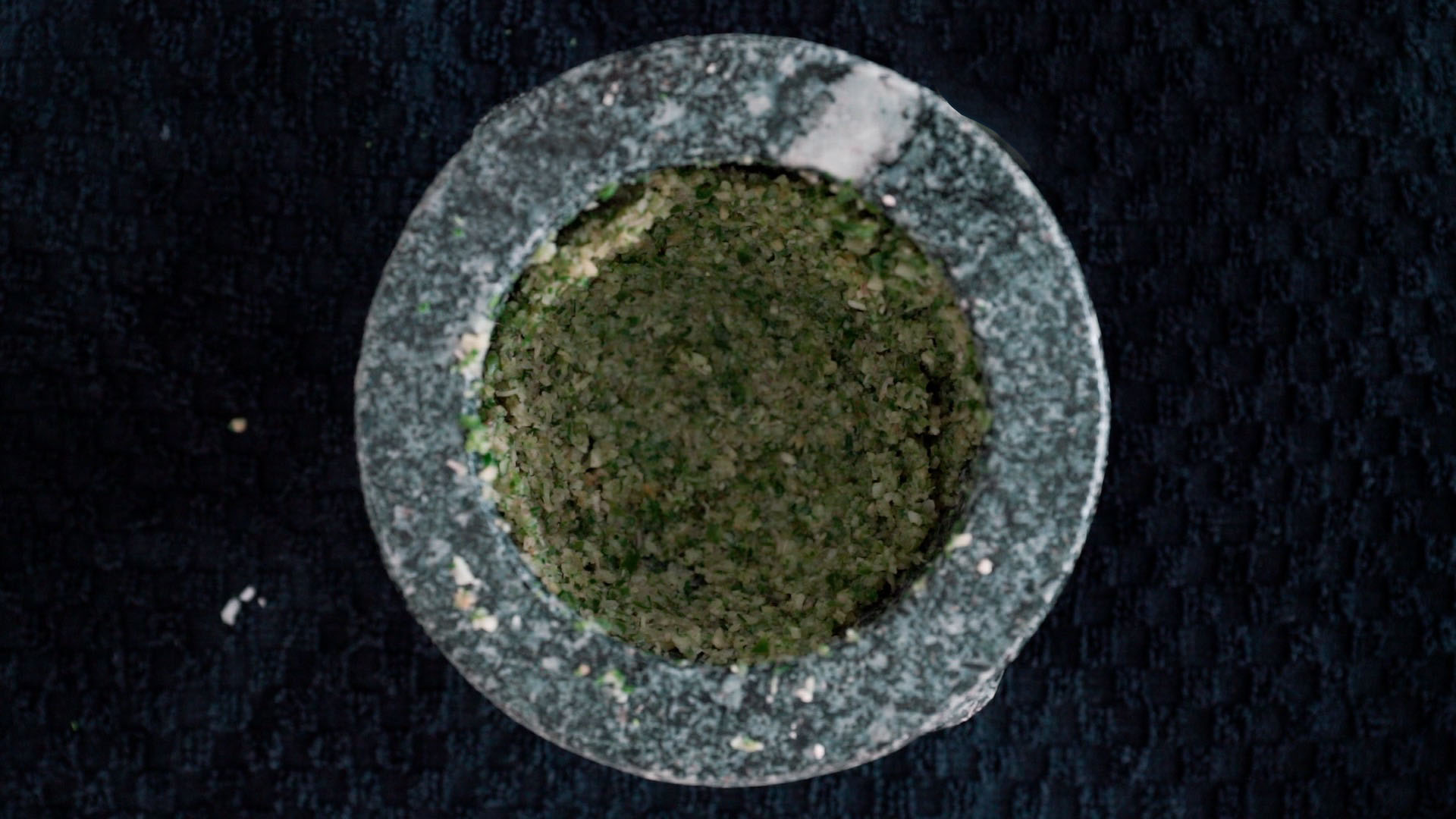 Green curry paste in mortar with still a course paste.