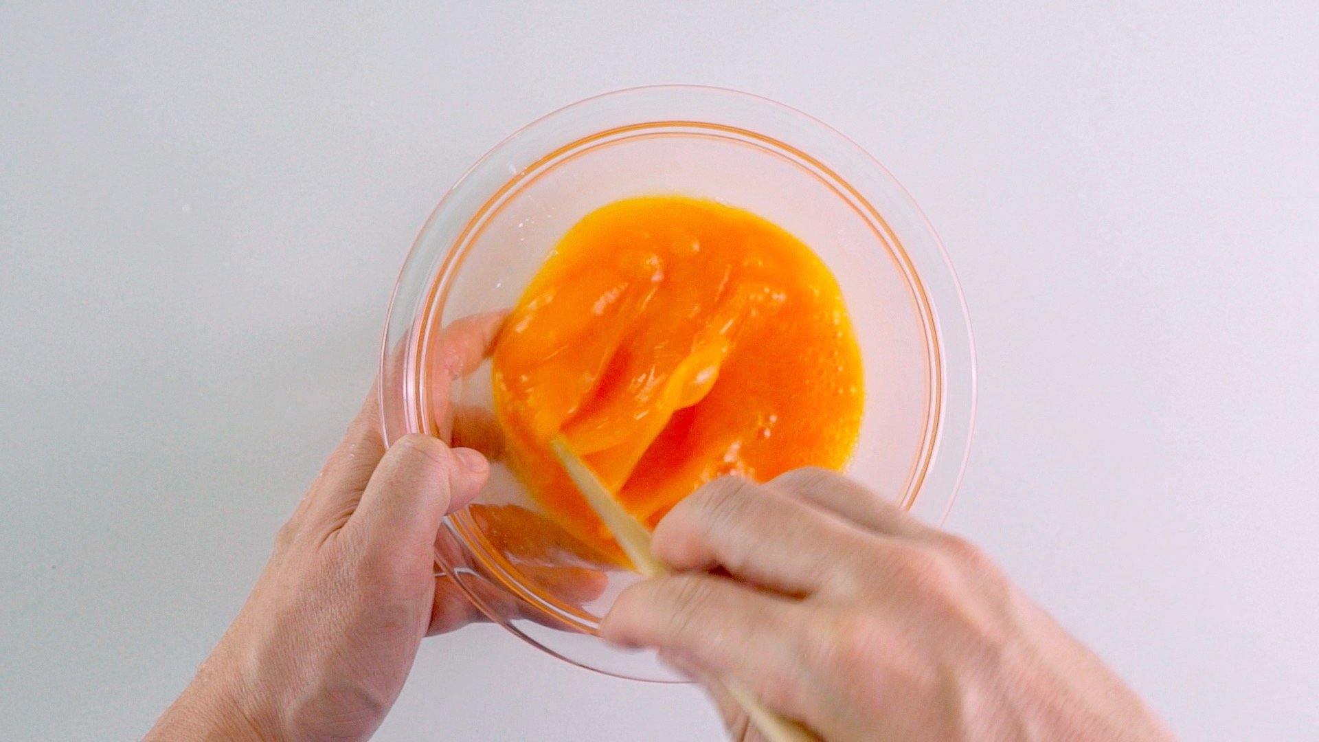 Beating eggs in a glass bowl with chopsticks.