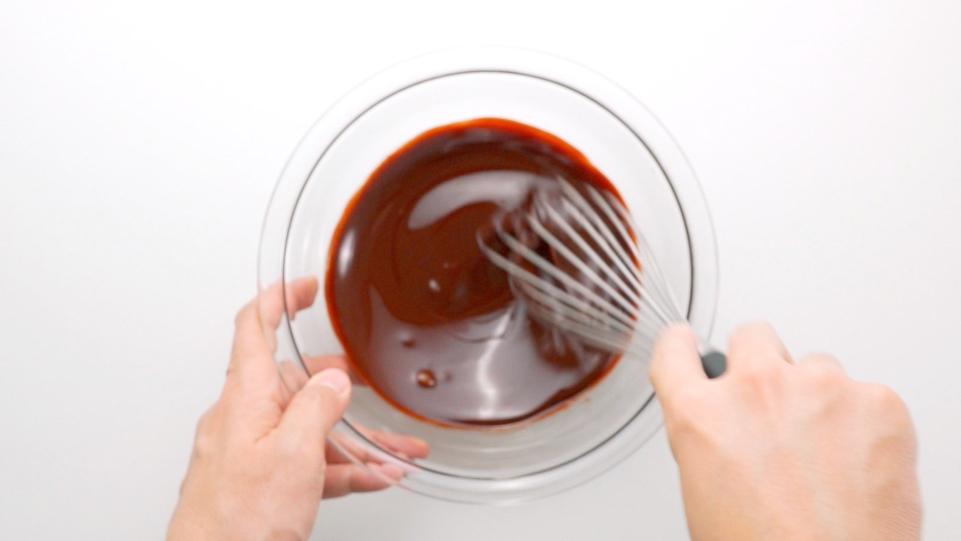Whisking melted butter and chocolate together in a glass bowl.