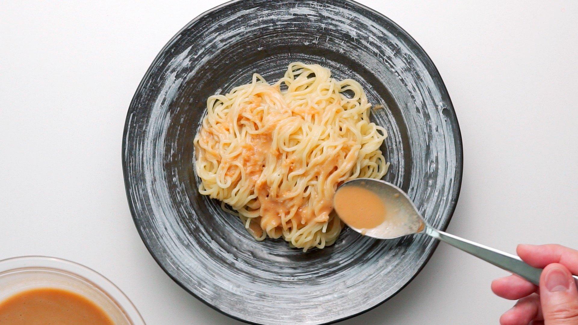 Dressing chilled ramen noodles with sesame dressing.
