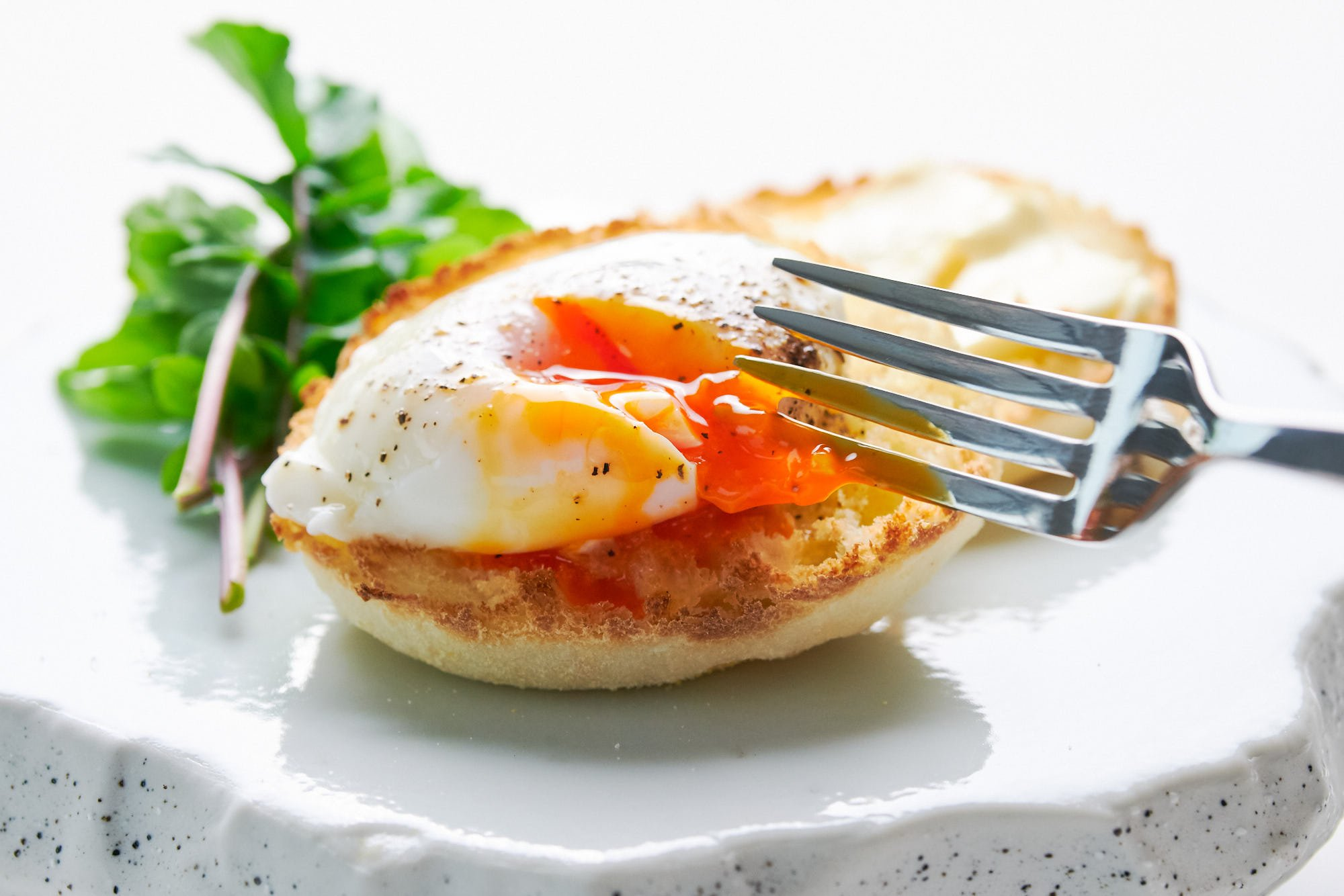 Breaking the yolk of a perfectly poached egg with a fork.