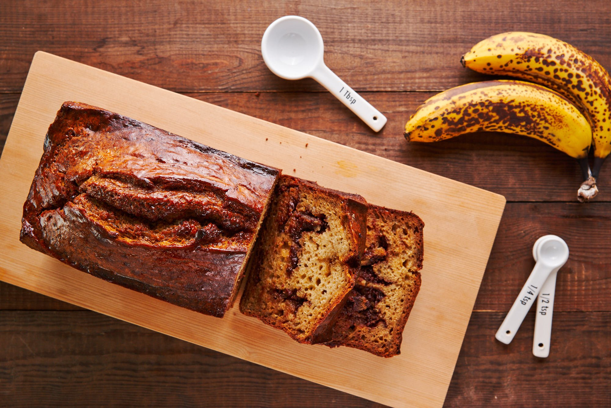 Slices of chocolate chunk banana bread on a wooden cutting board.
