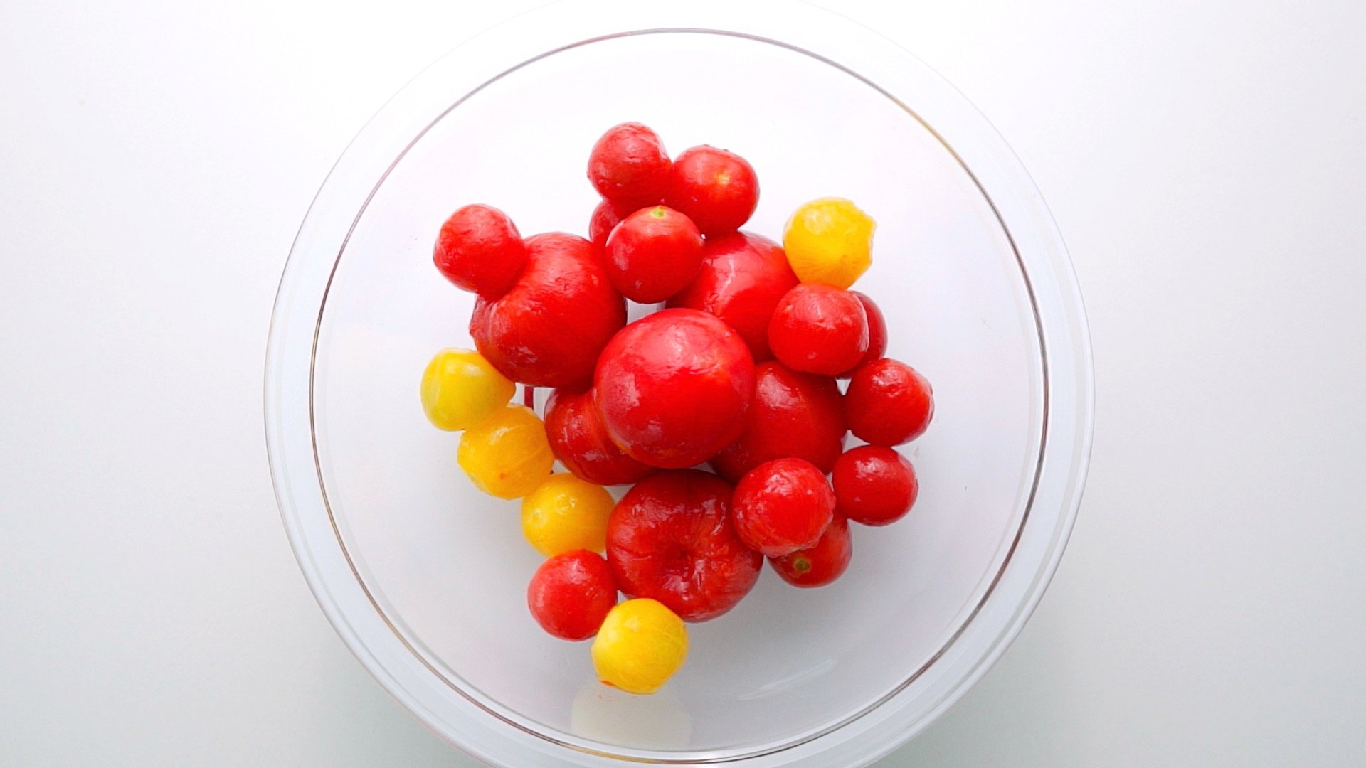 Overhead shot of a bowl of peeled tomatoes.