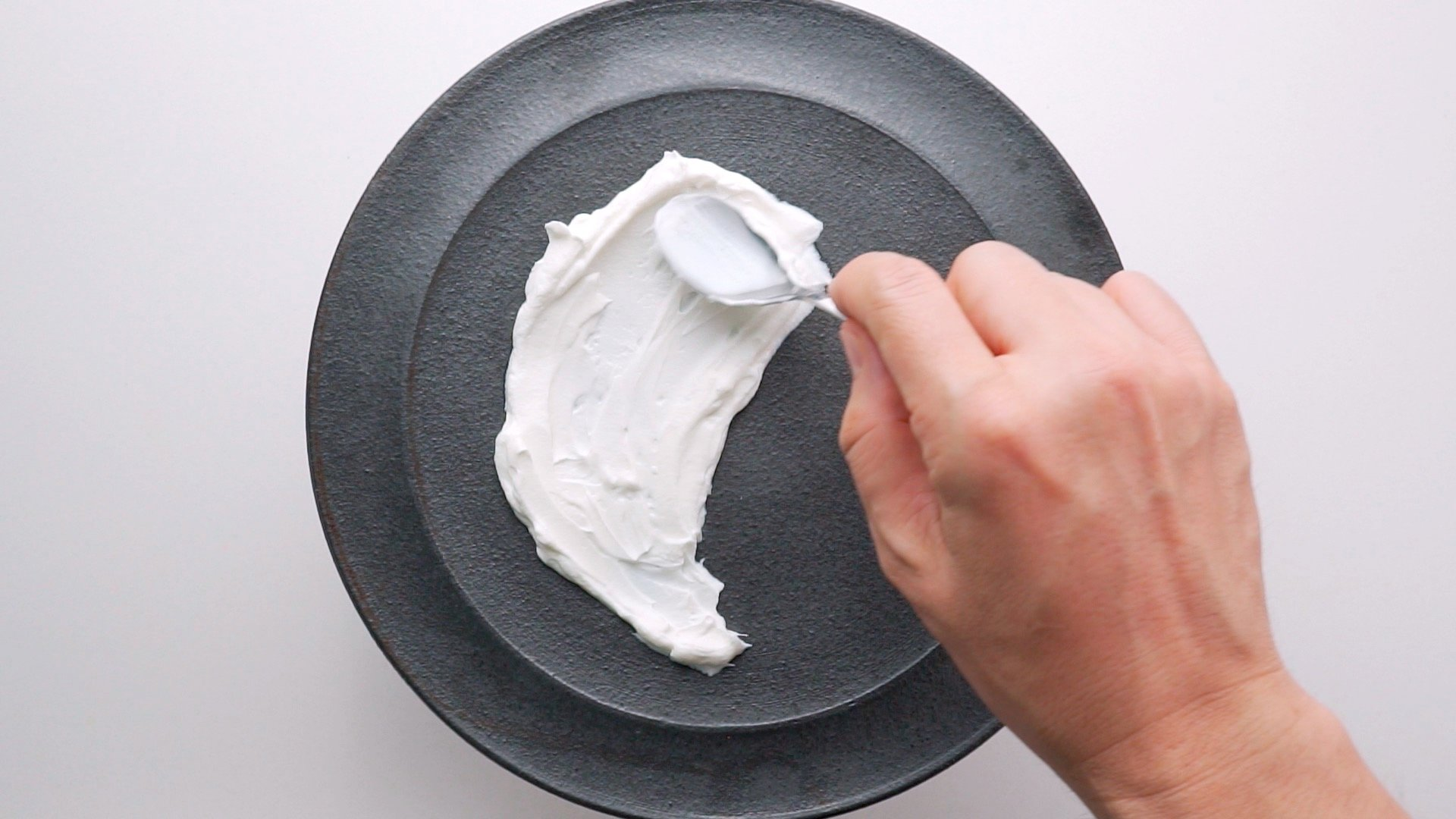 Spreading labneh on a plate.