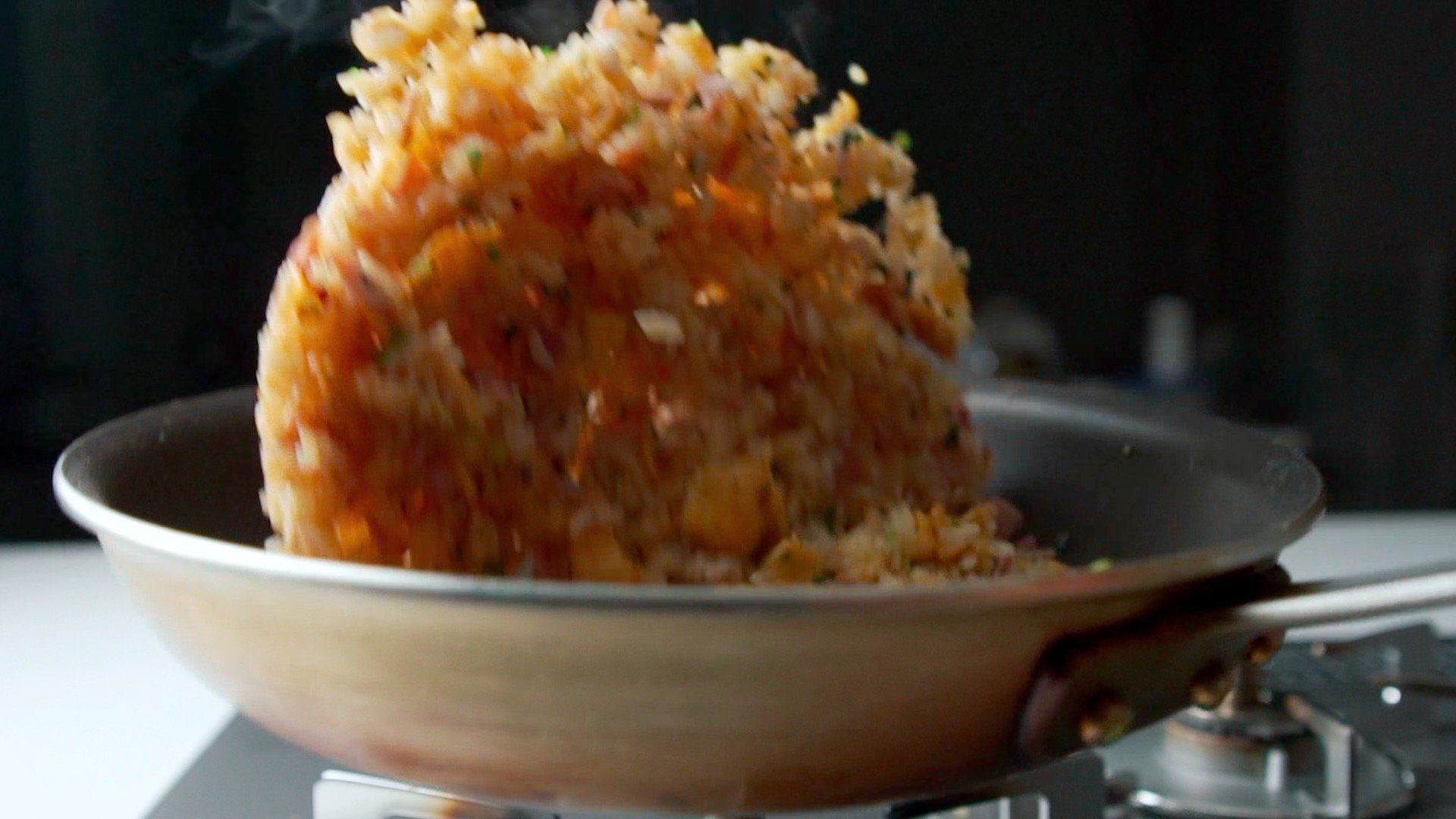 Tossing fried rice in a frying pan.
