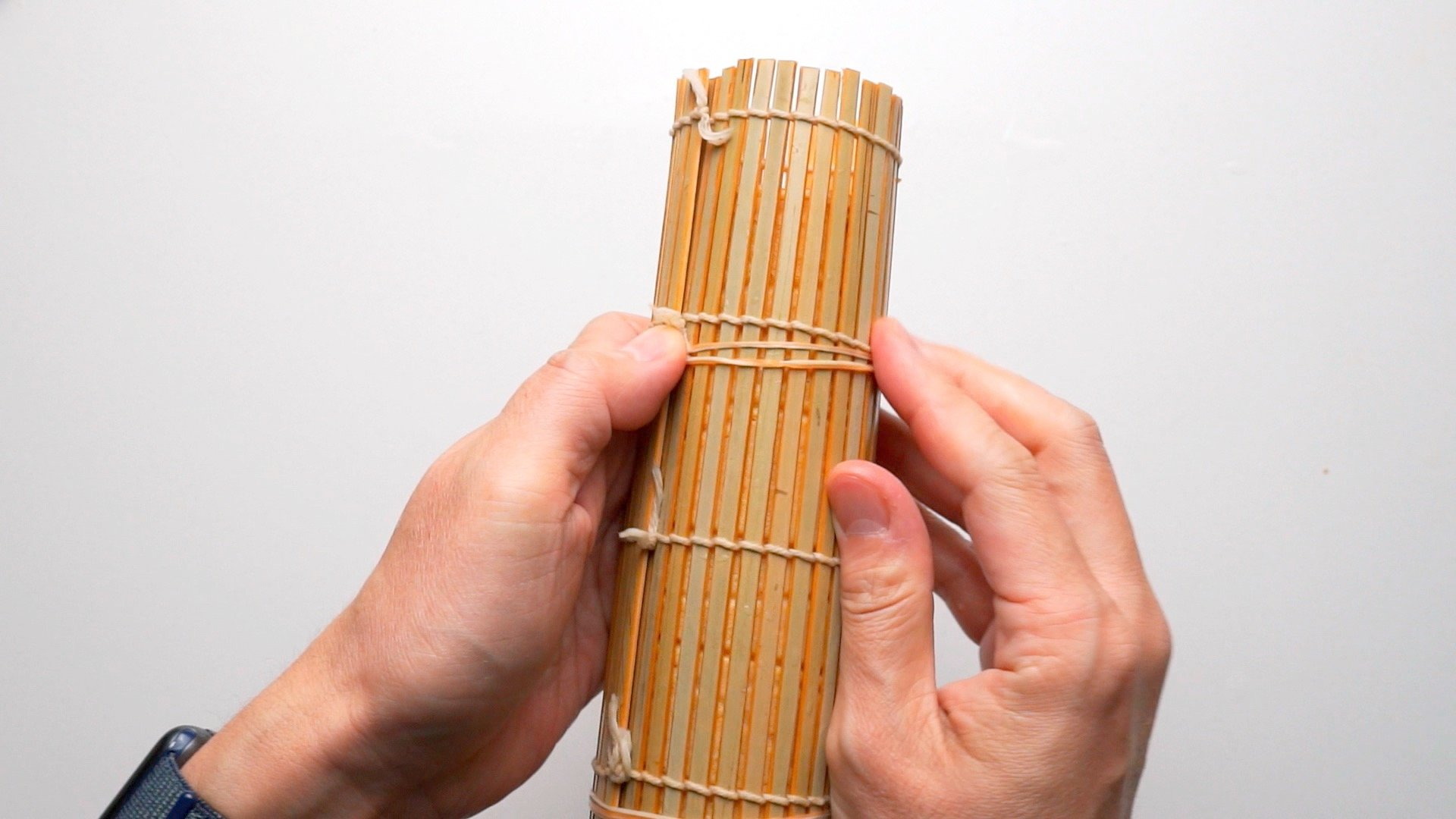 Compressing the rolled Datemaki using rubber bands.