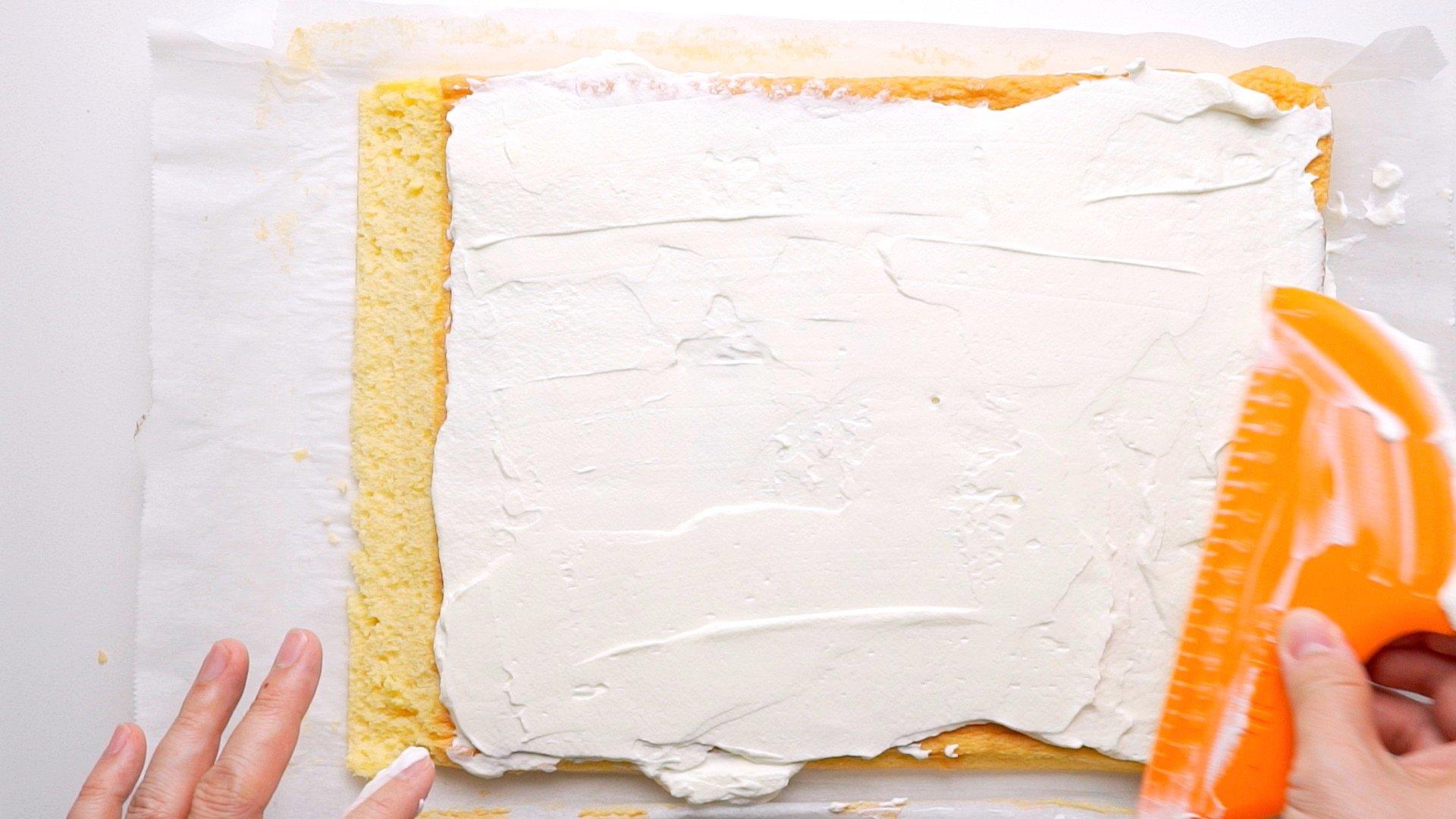 Spreading whipped cream onto sponge cake.