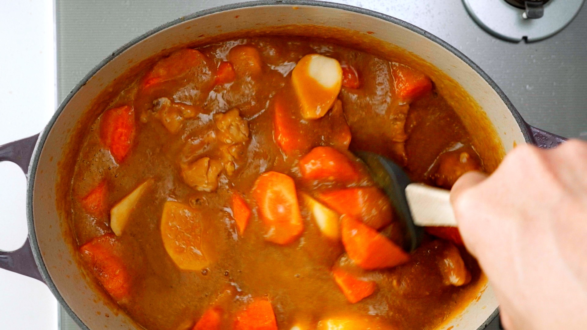 Stirring potatoes, carrots and chicken into the Japanese curry sauce.