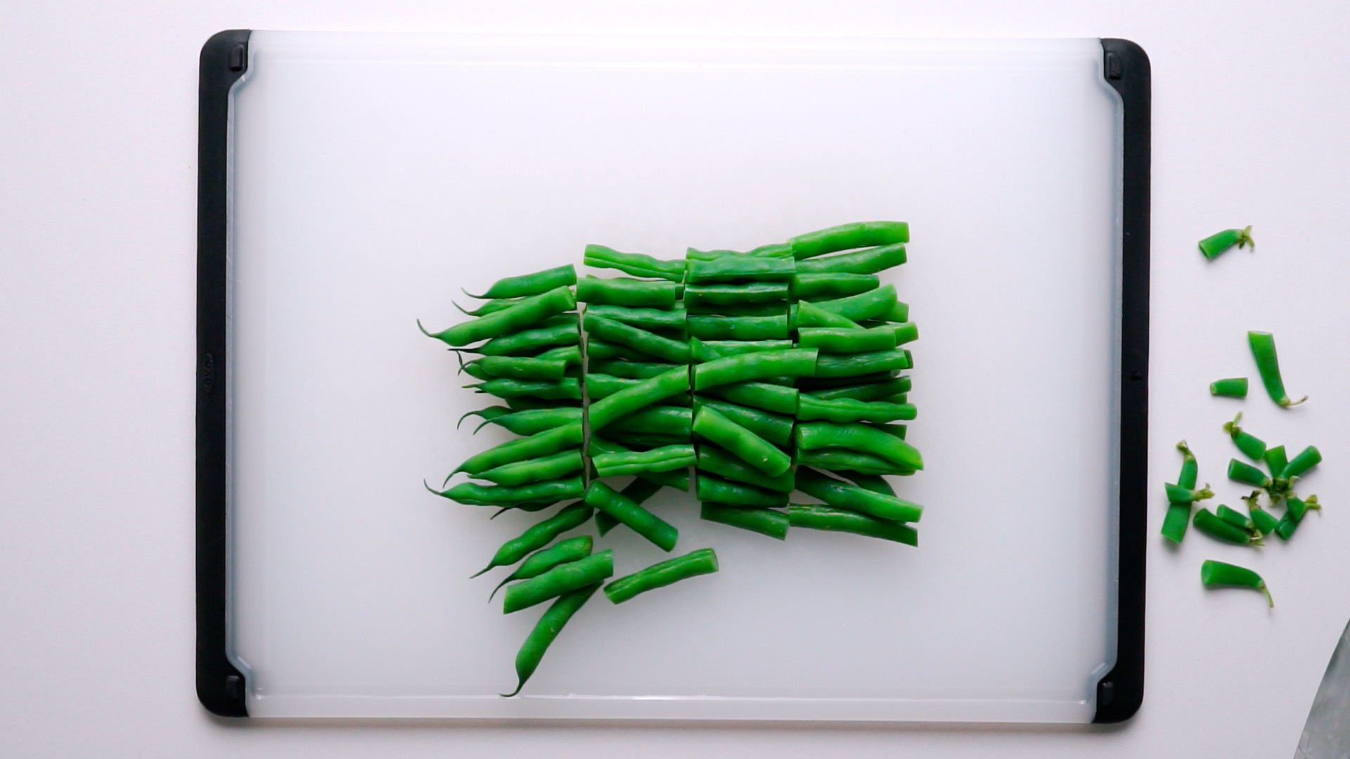 Chopped blanched green beans on cutting board.