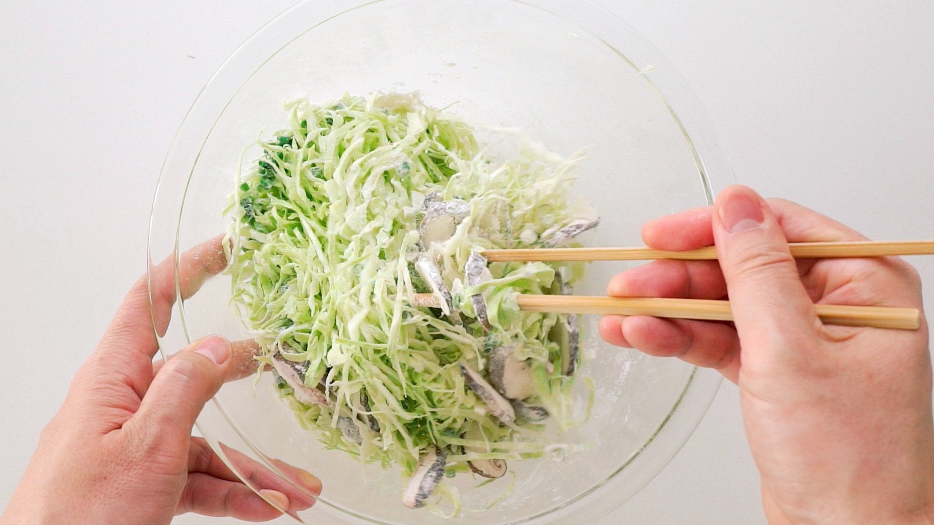 Mixing shredded cabbage, mushrooms and scallions together with flour.