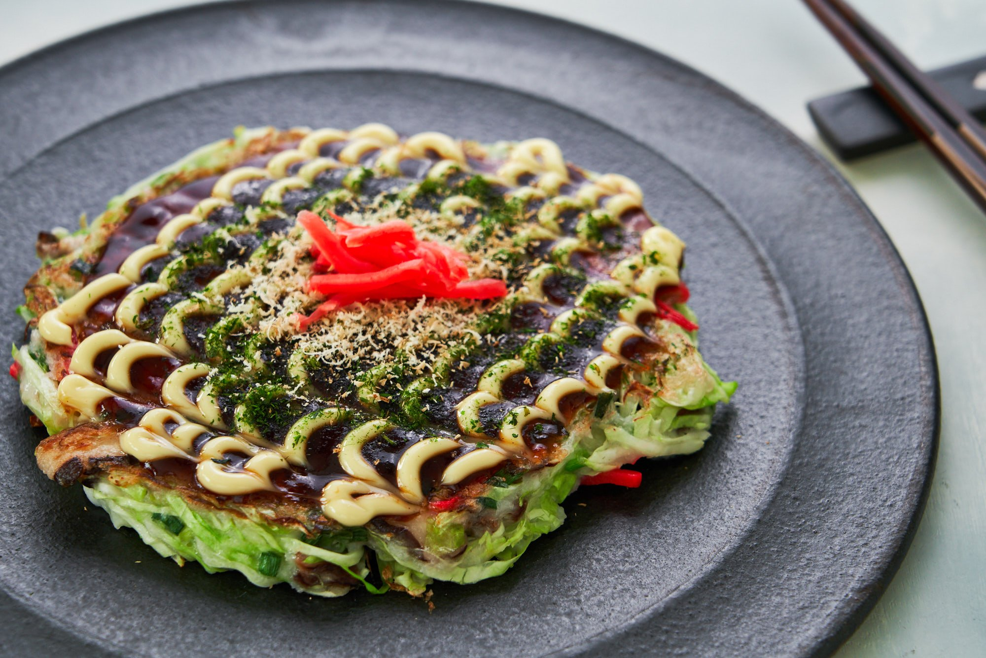 Okonomiyaki is a savory Japanese pancake that's made with a cabbage-based batter and it can be customized like a pizza with your favorite mix-ins and toppings.