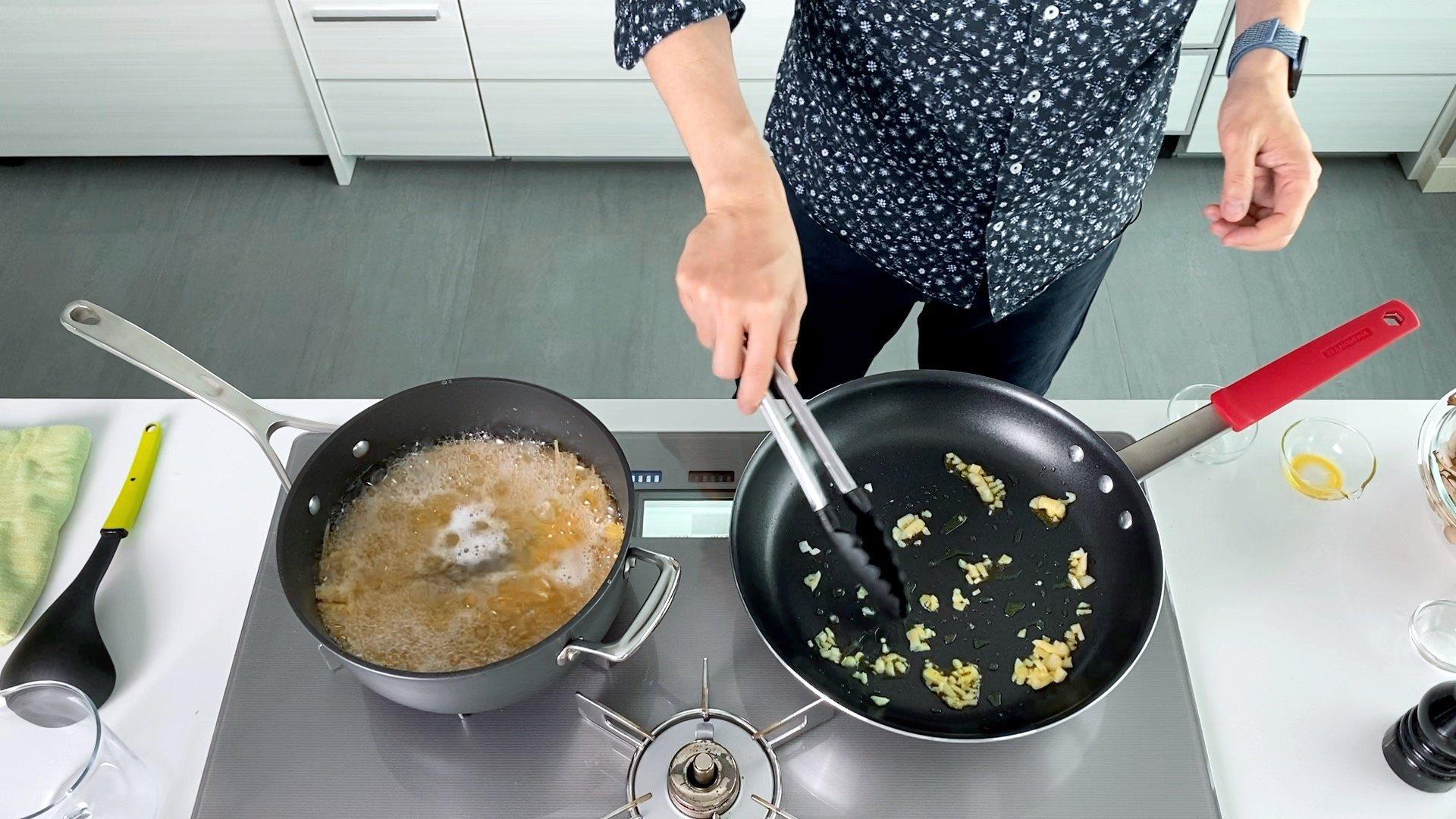 Sautéing garlic in a frying pan for pasta.