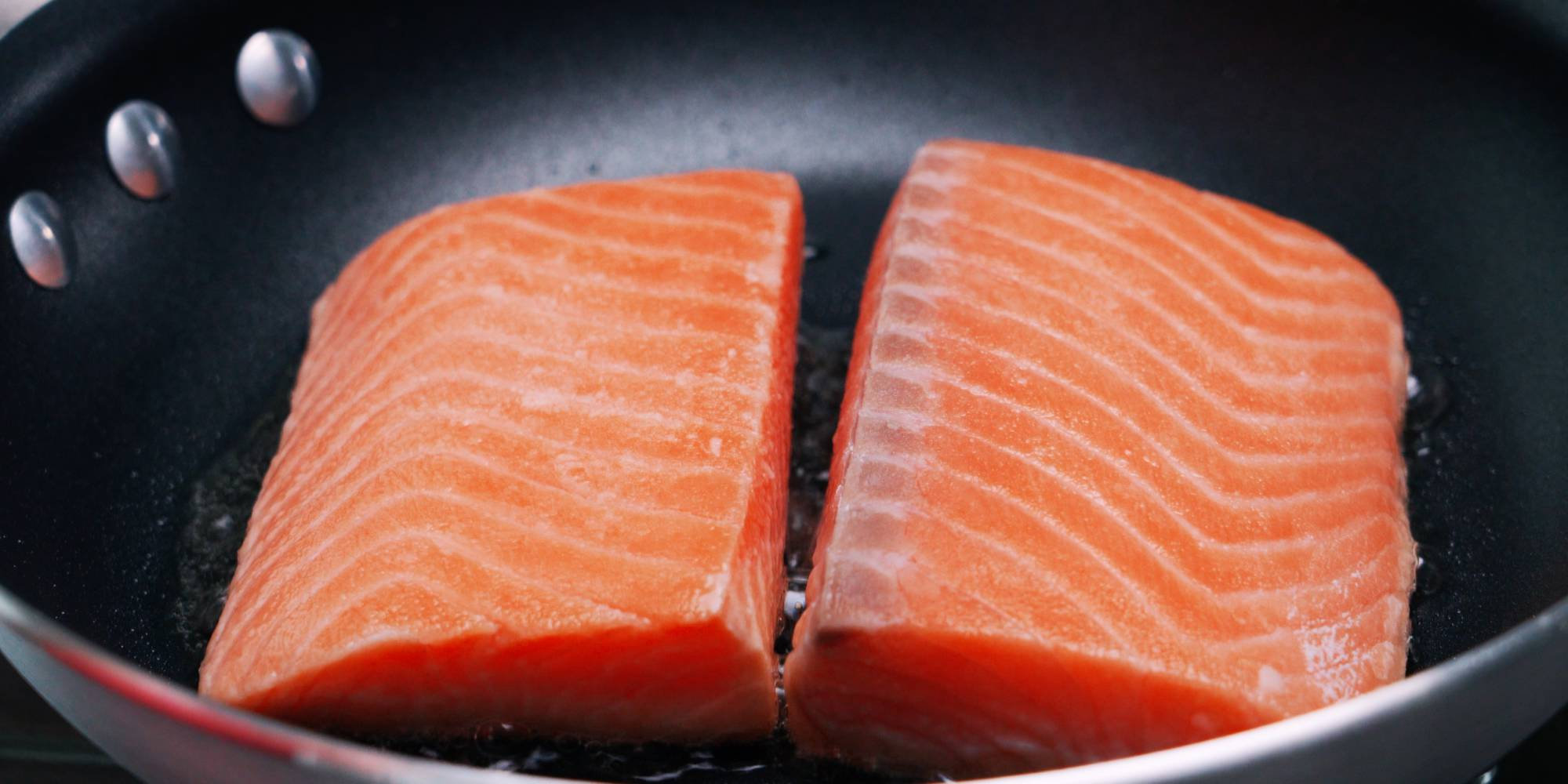 Salmon filets frying in a pan.