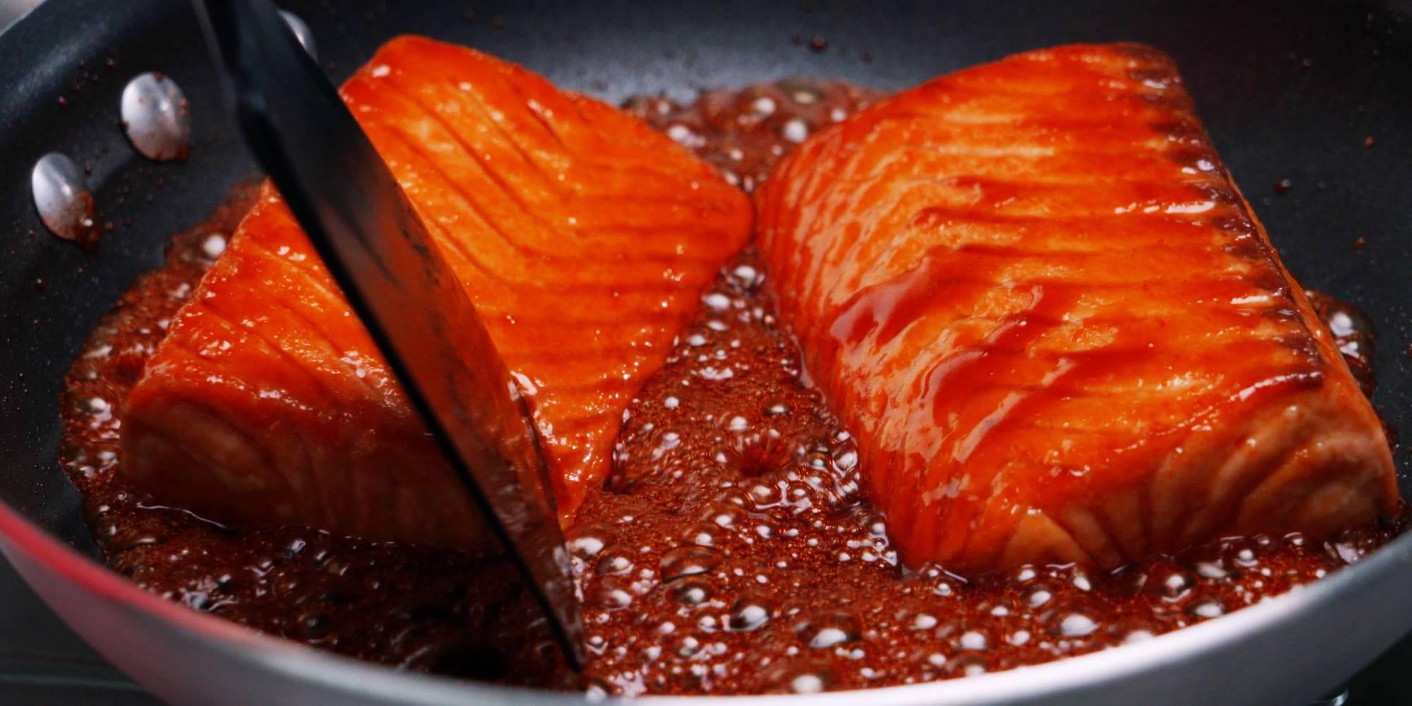Teriyaki salmon being glazed with teriyaki sauce.