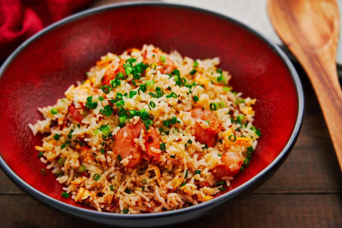 Best shrimp fried rice in a red bowl on a dark wooden table.